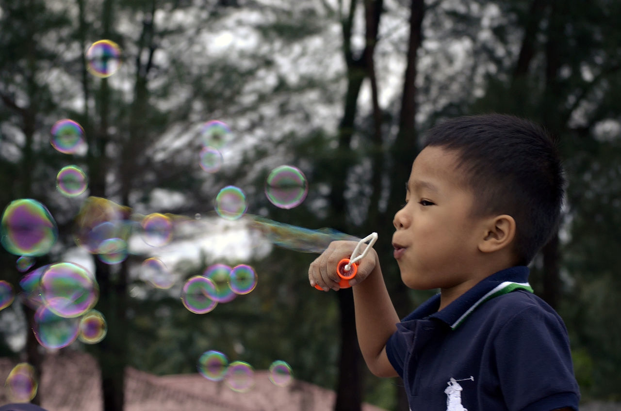 bubble wand, bubble, childhood, blowing, boys, soap sud, leisure activity, one person, real people, holding, casual clothing, focus on foreground, outdoors, lifestyles, day, elementary age, fragility, park - man made space, fun, headshot, mid-air, enjoyment, motion, standing, one boy only, tree, happiness, playing, close-up, nature, freshness