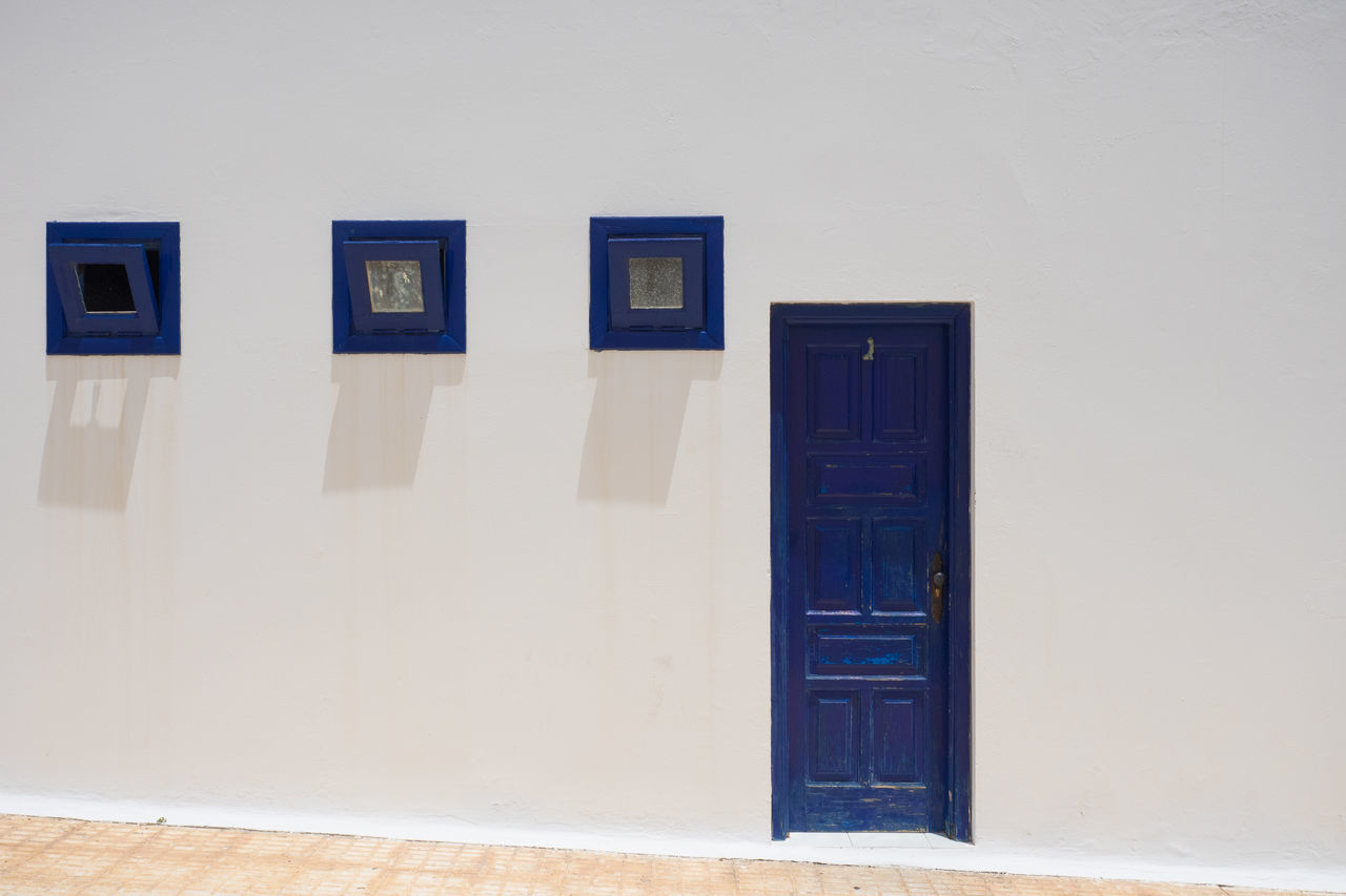 A blue door and three blue windows Blue Door Blue Window Blue Windows Built Structure Day Door No People Outdoors Shadow Sunny Toilet Window