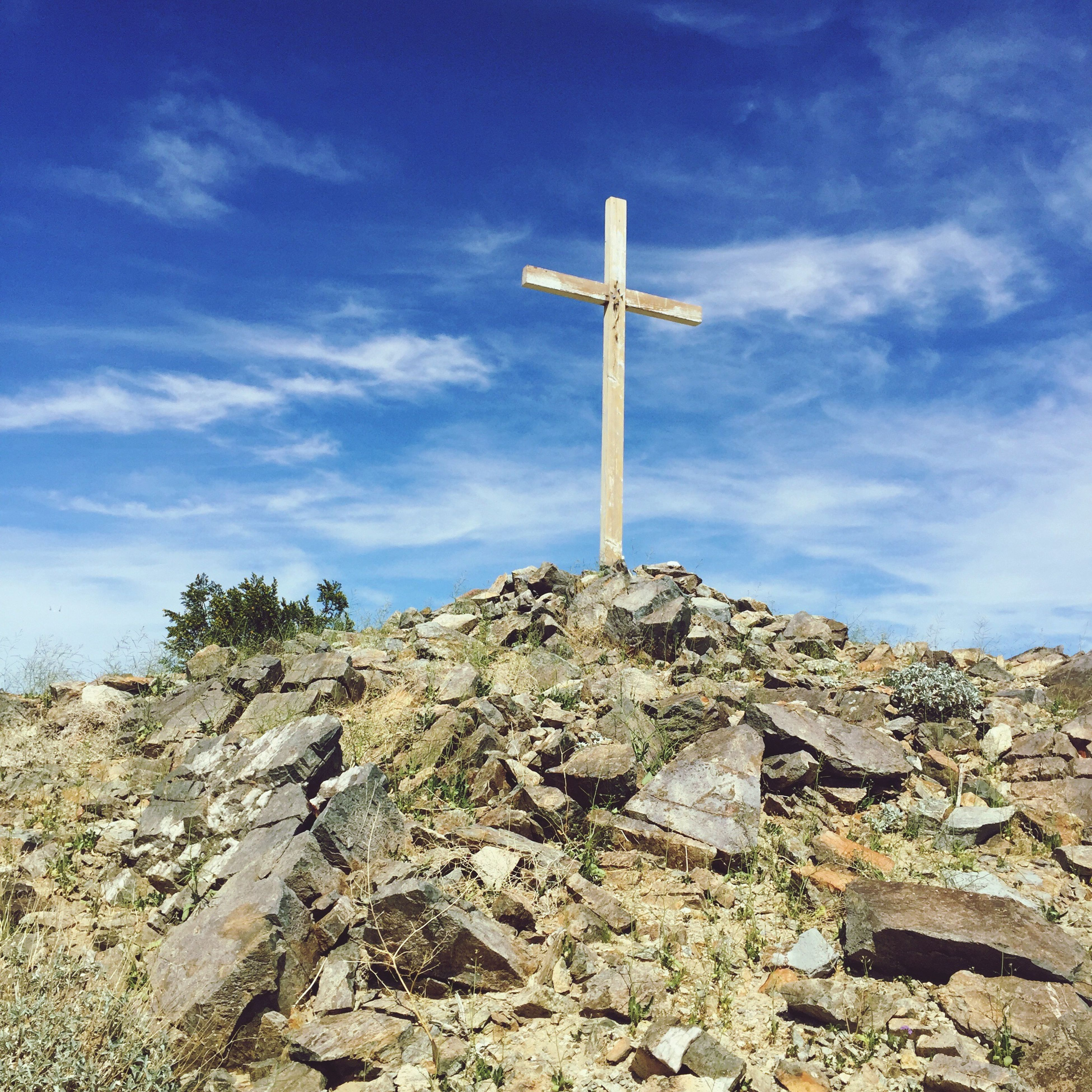 sky, low angle view, cloud - sky, tranquility, cross, blue, rock - object, cloud, nature, tranquil scene, day, landscape, mountain, spirituality, outdoors, non-urban scene, no people, scenics, beauty in nature, religion