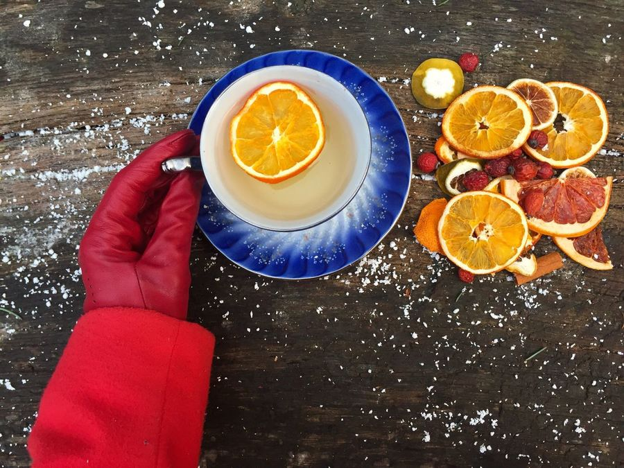 Woman hands wearing red gloves holding mug of orange tea placed on snowy table decorated with mistletoe and orange slices Orange - Fruit Food And Drink Lemon Table Fruit Citrus Fruit SLICE Freshness Close-up Hand Woman Gloves Hold Cup Glass Drink Tea Snow Winter Table Oranges Slices Red Gloves
