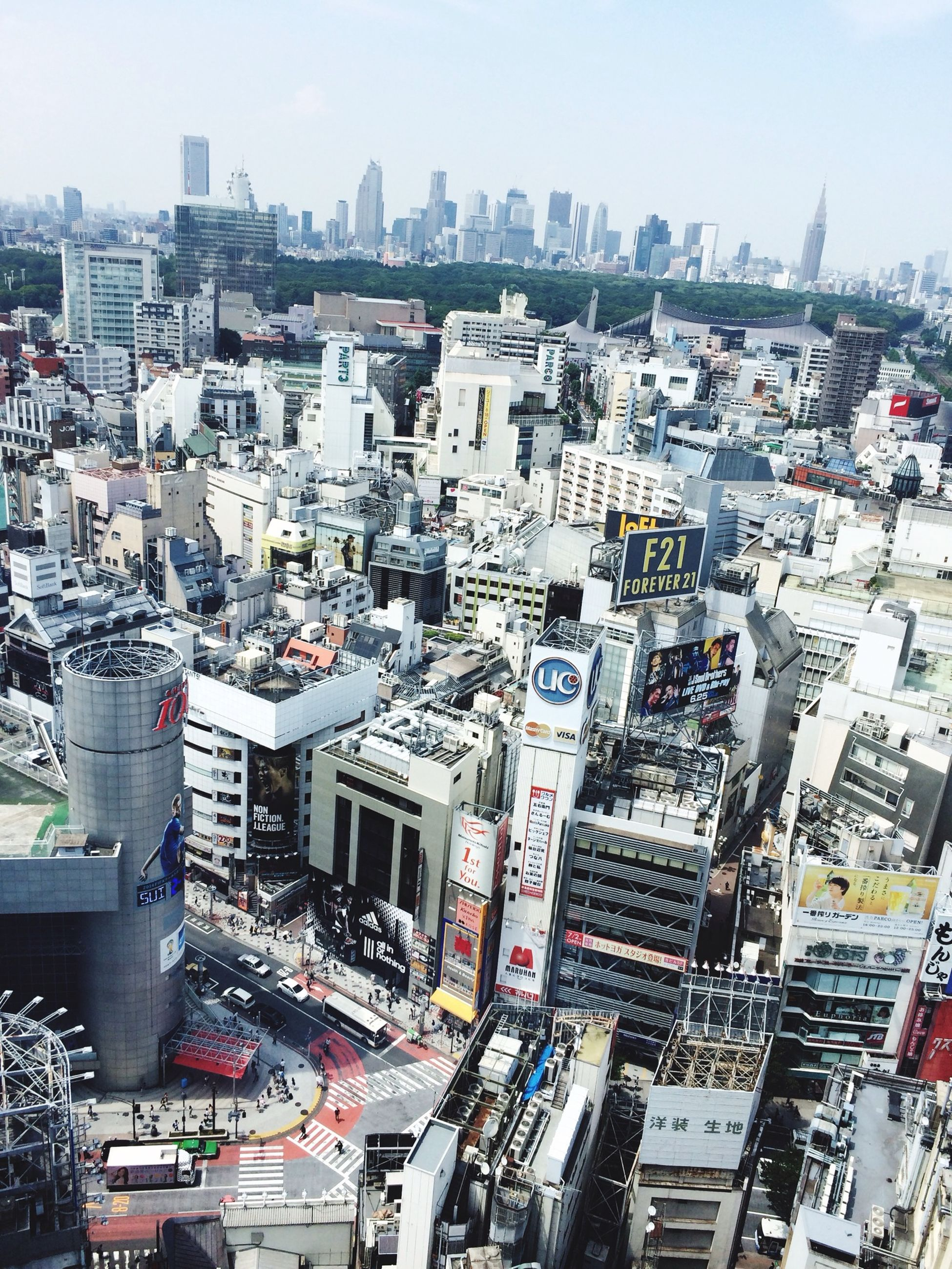 building exterior, city, architecture, built structure, cityscape, high angle view, crowded, car, city life, transportation, residential district, residential building, street, land vehicle, skyscraper, residential structure, day, mode of transport, tall - high, sky