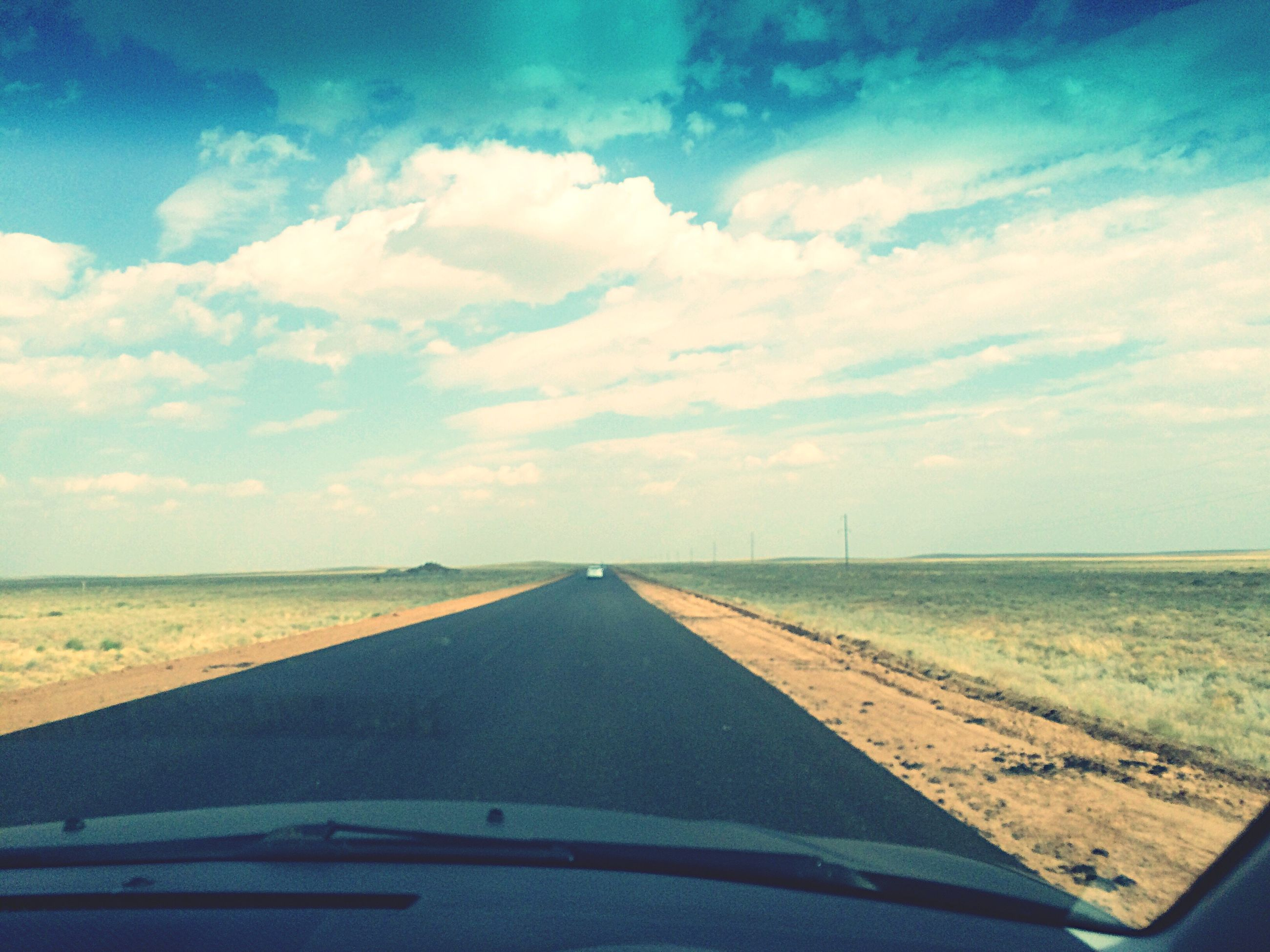 transportation, the way forward, road, sky, diminishing perspective, vanishing point, tranquil scene, cloud, landscape, empty, sea, tranquility, cloud - sky, day, long, outdoors, nature, horizon over land, blue, summer, scenics, ocean, straight, cumulus cloud, non-urban scene, vacations