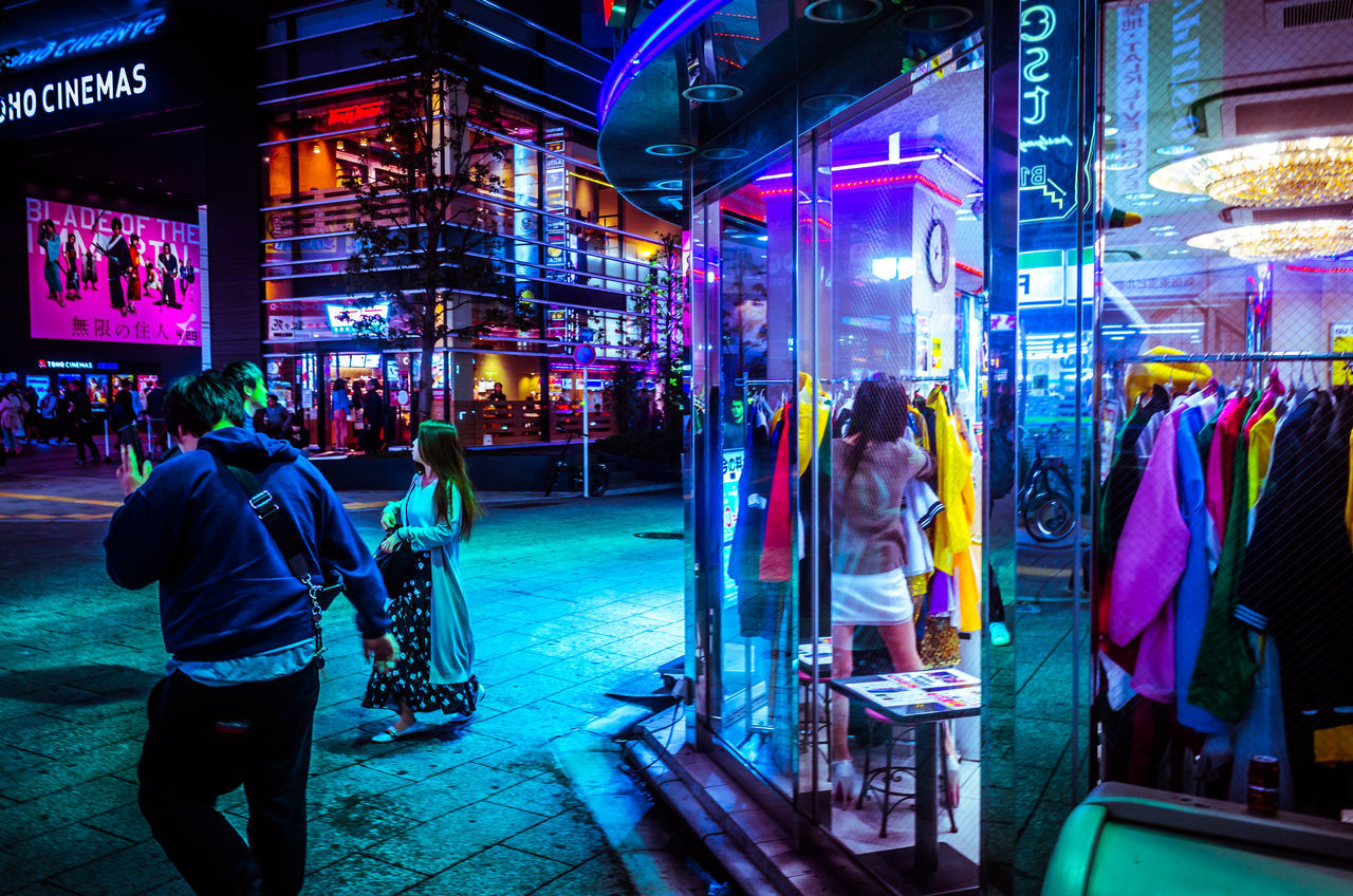 night, illuminated, real people, men, city, architecture, lifestyles, nightlife, building exterior, neon, large group of people, women, modern, outdoors, adult, people