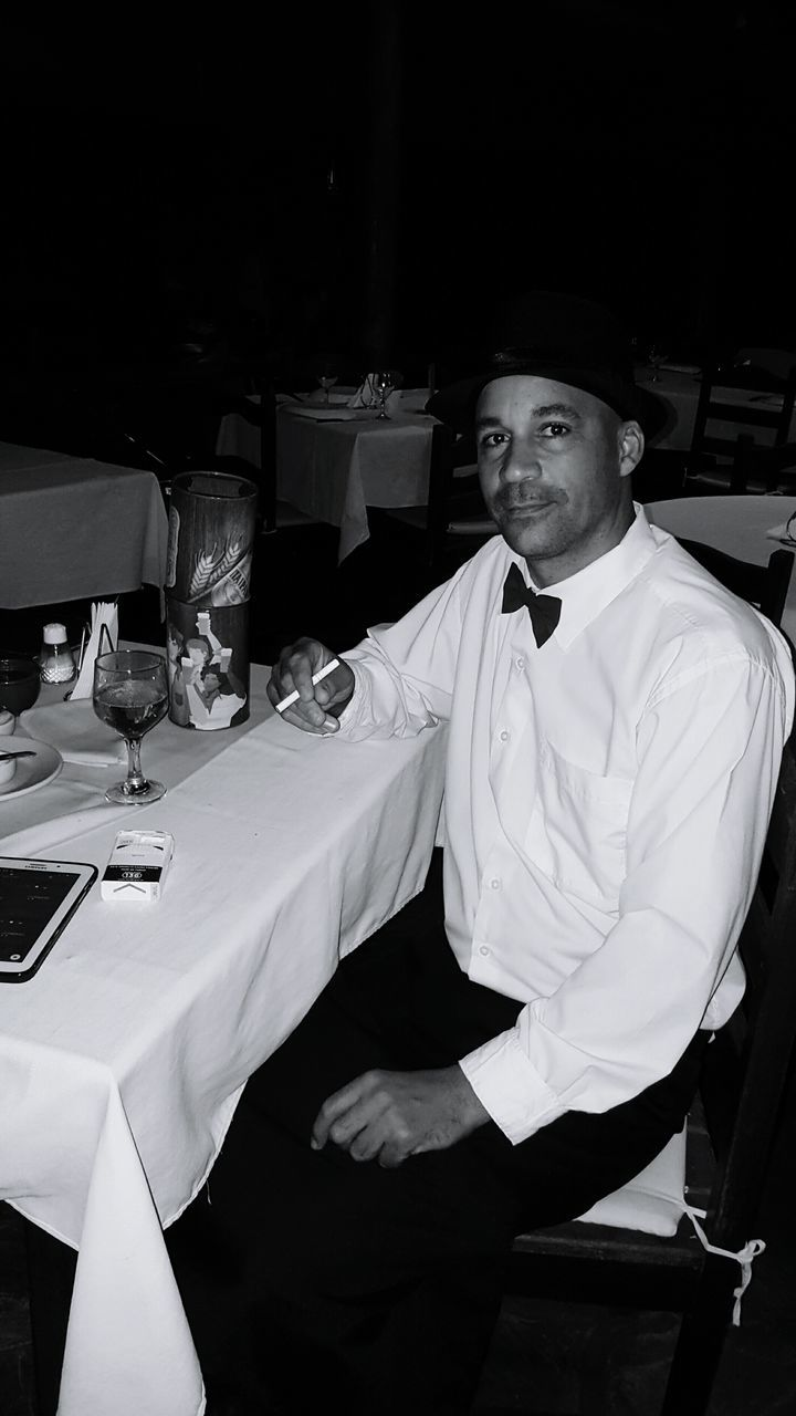 Portrait Of Man Holding Cigarette Sitting At Table In Restaurant