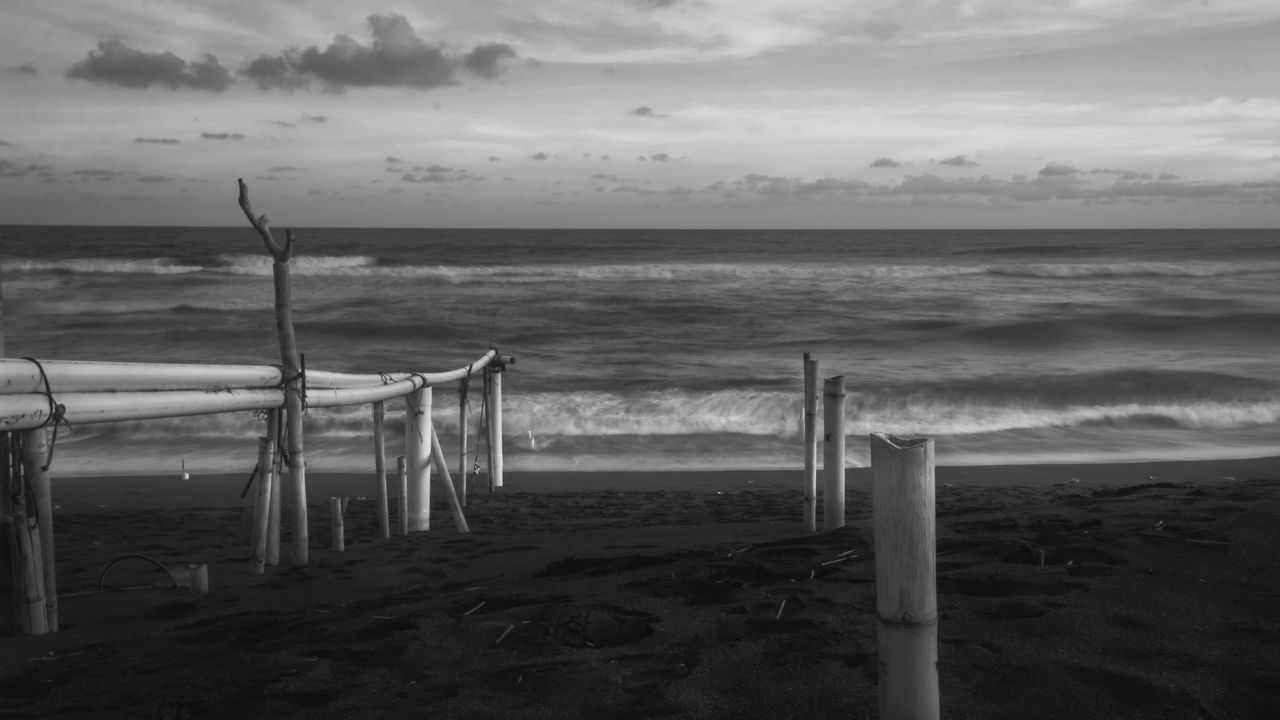 Wooden Posts On Sea Shore Against Sky