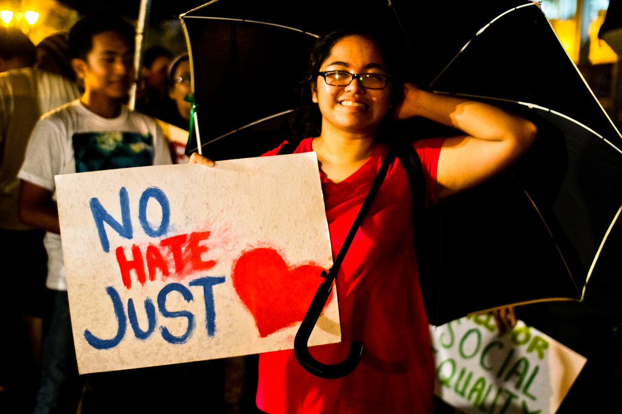 """A member of a youth group, inside a university in the Philippines, holds a sign, reading """"No Hate Just Love,"""" calling for social equality. CHRIS QUINTANA Adult Adults Only ASIA Equal Rights  Equality Equality For All Eyeglasses  GenderEquality Happiness Night One Person Only Men Outdoors People Social Issues Society Women Youth Culture Youth Of Today"""