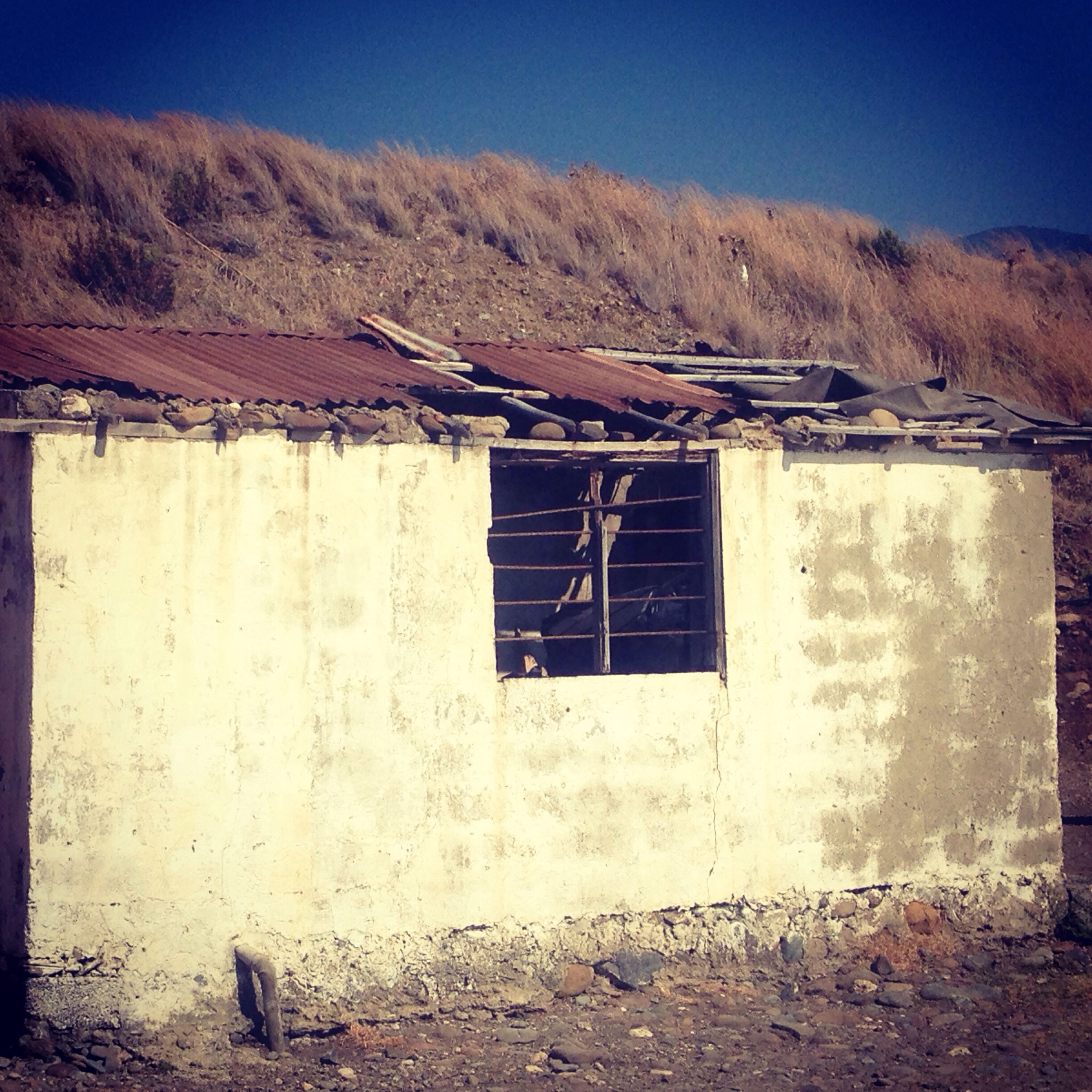 built structure, architecture, building exterior, house, window, clear sky, abandoned, old, obsolete, damaged, day, sky, no people, mountain, outdoors, sunlight, deterioration, residential structure, run-down, roof