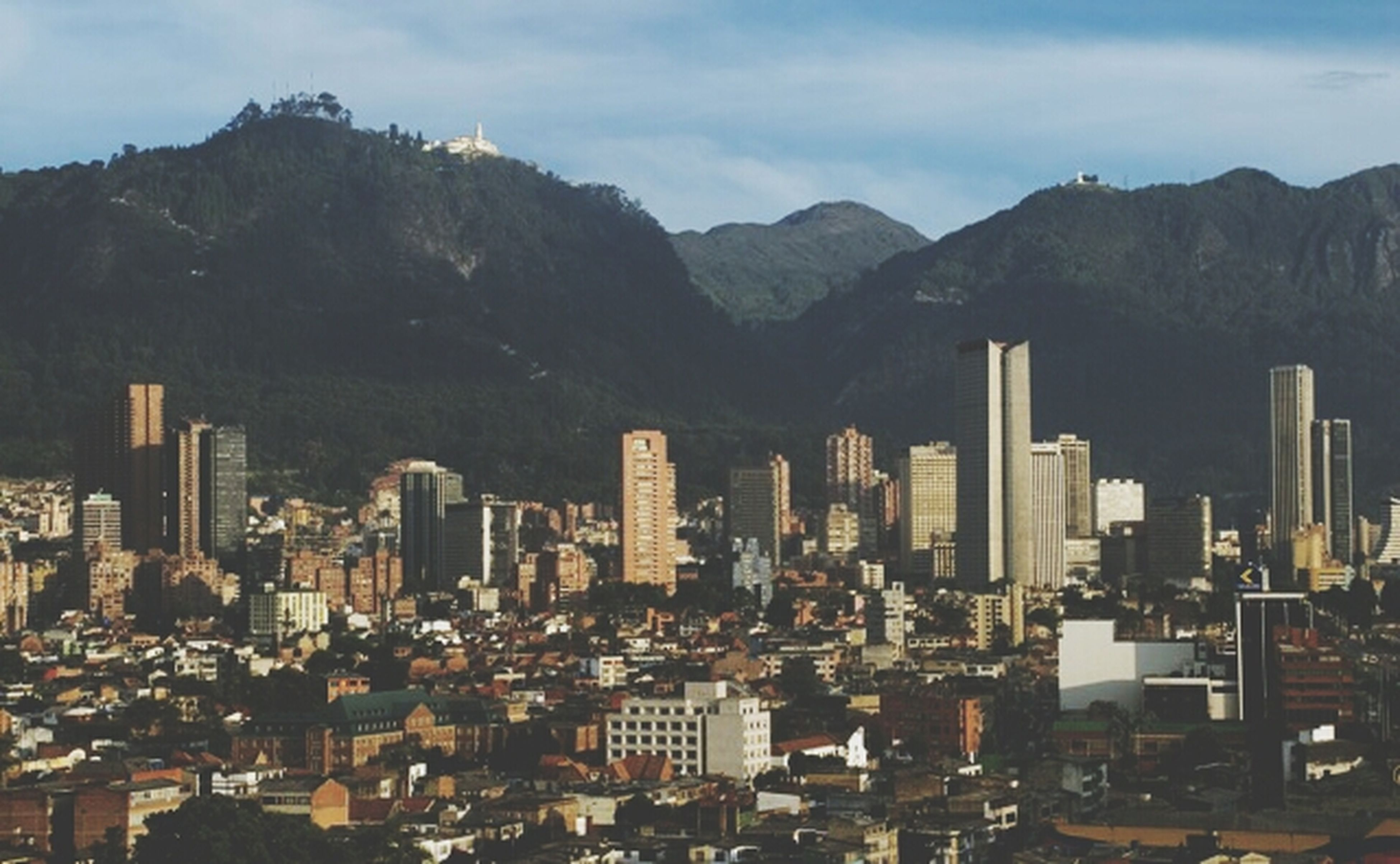 mountain, building exterior, architecture, built structure, city, sky, mountain range, cityscape, cloud - sky, residential building, residential district, high angle view, crowded, residential structure, cloud, day, outdoors, no people, nature, skyscraper