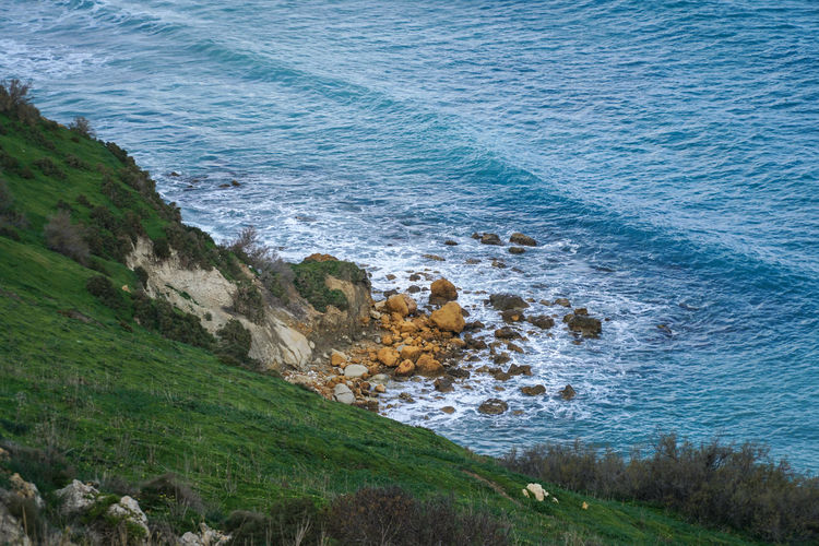 Tiny rocky beach - next to high slope - cliffs coastline Beach Beauty In Nature Coast Coastline Current Gozo High Landscape Loneliness Malta Meadows Natural Nature Nature Outcast Outdoors Rock Rocky Sea Shore Slope Stones Water Waves Wild