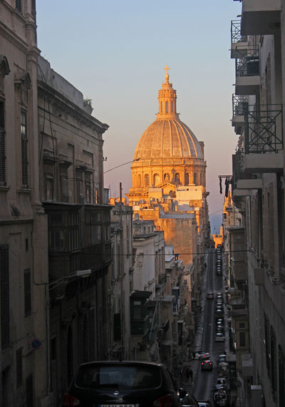 Golden evening light on a church dome in Valletta, Malta Valletta Malta No People Golden Light Sunset Our Lady Of Mount Carmel Old Mint Street Up And Down Steep Street Narrow Cars Traffic Sea Travel Destinations Vacation Architecture City Town Capital History Illuminated Sky Outdoors