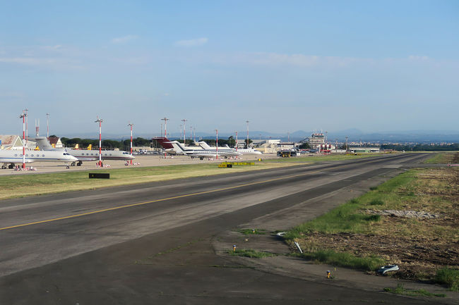 Rome Italy 19 June 2016. Private jets parked by the runway of Ciampino airport. The air traffic control of Aeroporto G. B. Pastine is visible in the background. Shot from inside airplane window. Aeroporto G. B. Pastine Air Traffic Control Tower Airport Airport Photography Airport Runway Airport Waiting Airportlife Airportphotography Airports Aviation Aviationphotography Capital Cities  Flights From Rome Flights To Rome Italia Italy Jets Mode Of Transport Private Jets Roma Rome Airport Rome Ciampino Airport Rome, Italy Runway Sky