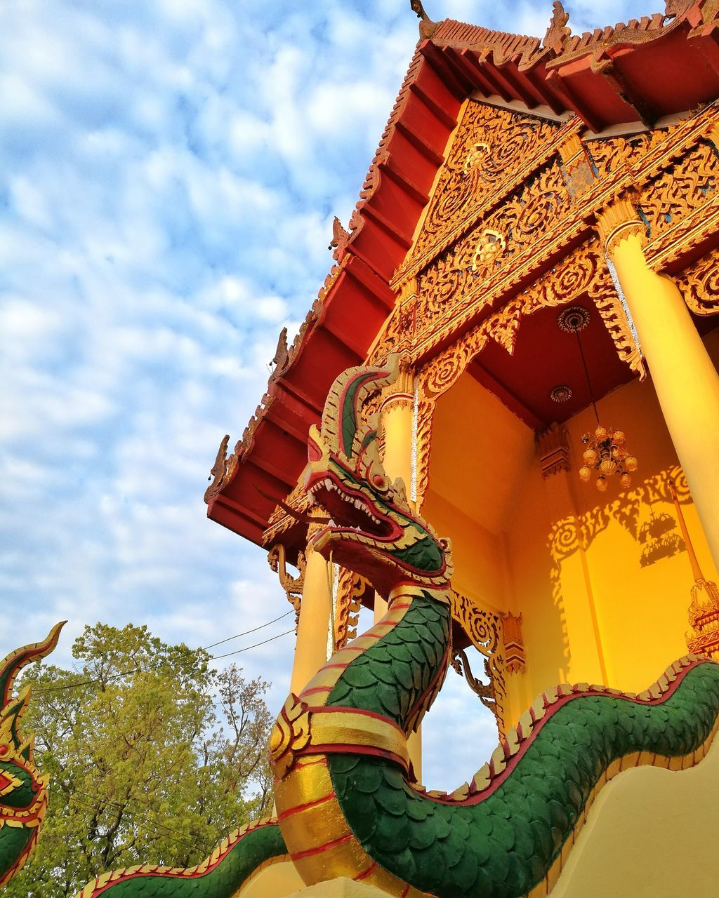 low angle view, religion, spirituality, place of worship, cultures, sky, day, outdoors, statue, dragon, multi colored, architecture, no people, tree, chinese dragon