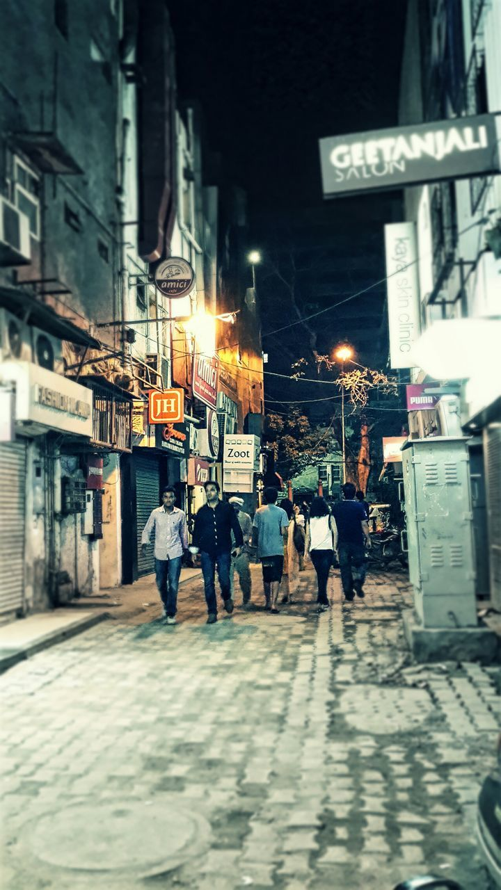 building exterior, architecture, built structure, illuminated, city, real people, men, street, night, walking, city life, outdoors, women, large group of people, group of people, lifestyles, road, full length, crowd, people