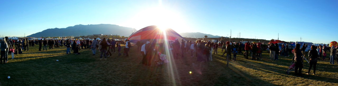 Hot Air Balloon Amidst People Against Sky On Sunny Day