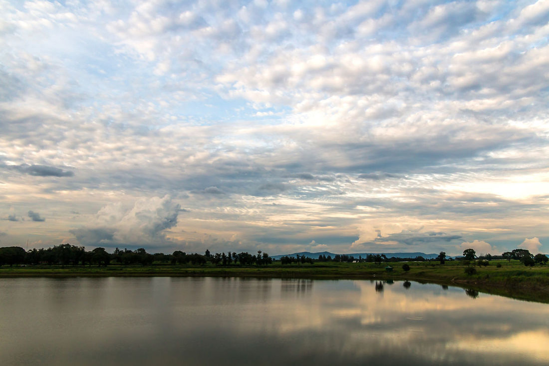 Landscape in cloudy day with fluffy cloud Background; Beauty In Nature Blue Sky; Building Exterior Cloud - Sky Cloudy; Day Evening; Fluffy Cloud; Grass; Landscape; Mountain; Nature No People Outdoors Pond; Reflection Scenics Sky Sunset Tree Tropical; Water Waterfront White Cloud;