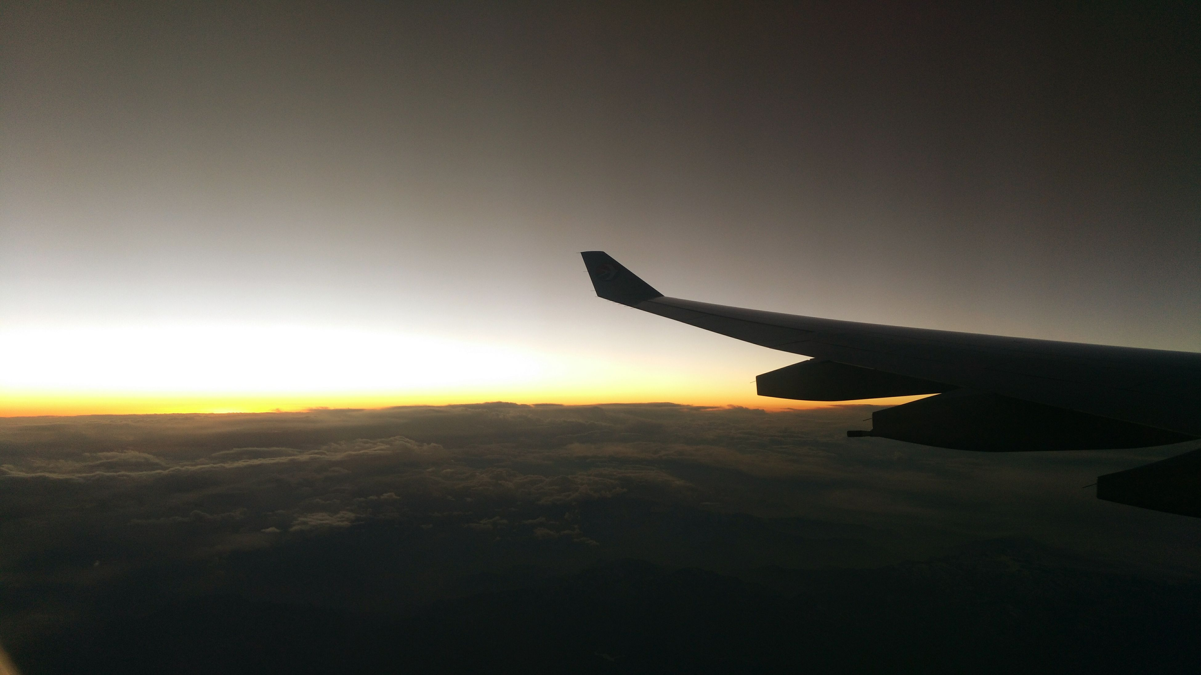 airplane, air vehicle, flying, transportation, mode of transport, sunset, aircraft wing, landscape, mid-air, sky, travel, scenics, beauty in nature, on the move, silhouette, journey, nature, copy space, aerial view, tranquil scene