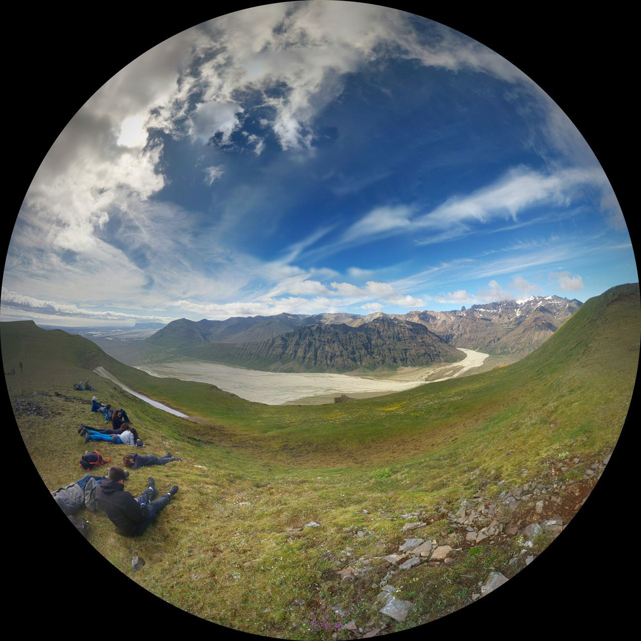 Fish-Eye Effect Of People Relaxing On Green Landscape By River Against Sky