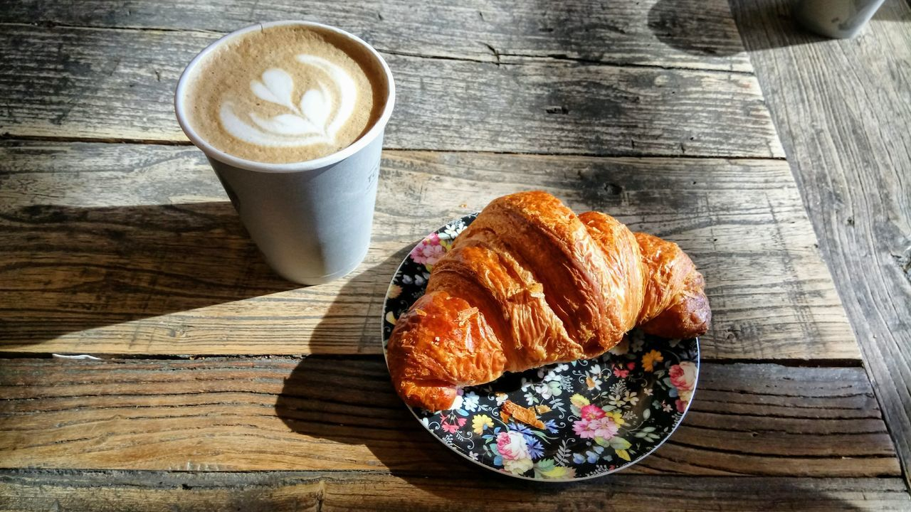 coffee - drink, coffee cup, croissant, food and drink, table, wood - material, cappuccino, drink, frothy drink, high angle view, refreshment, latte, breakfast, indoors, food, freshness, froth art, no people, french food, sweet food, close-up, cafe, day, ready-to-eat