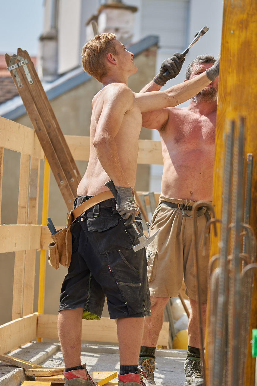 shirtless, real people, leisure activity, lifestyles, day, standing, men, workshop, outdoors, young adult