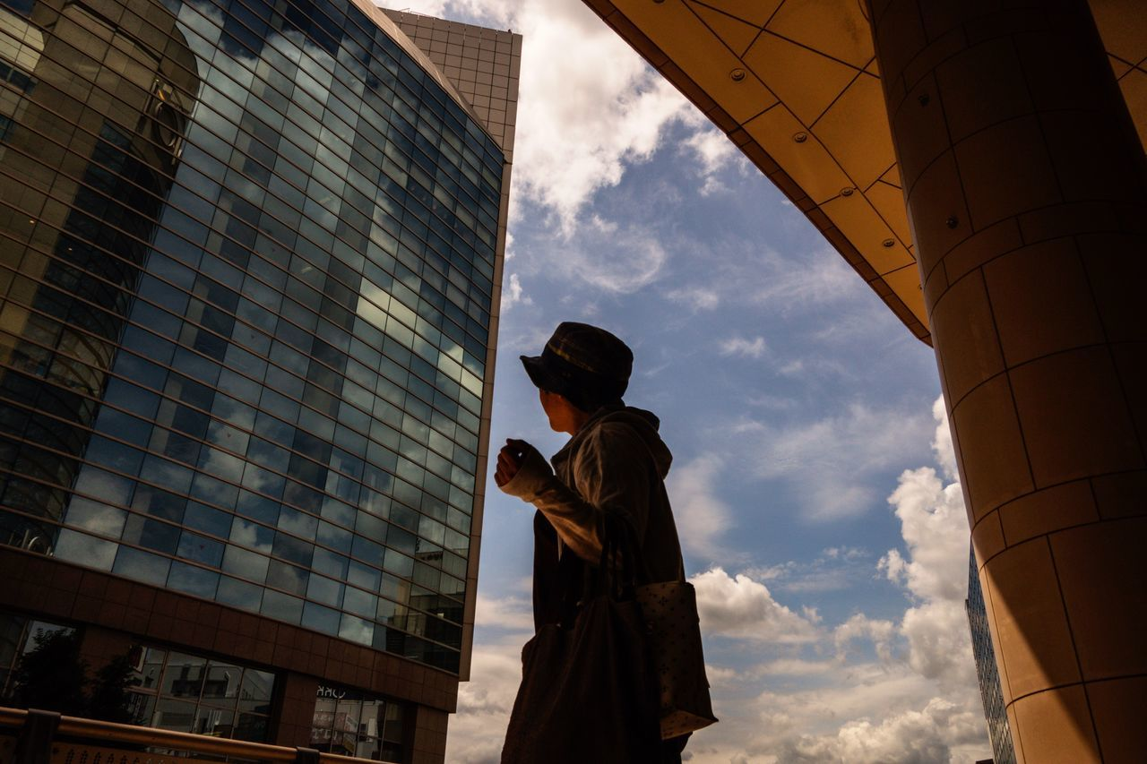 architecture, built structure, real people, building exterior, sky, men, one person, cloud - sky, low angle view, lifestyles, standing, rear view, city, outdoors, modern, day, skyscraper, people