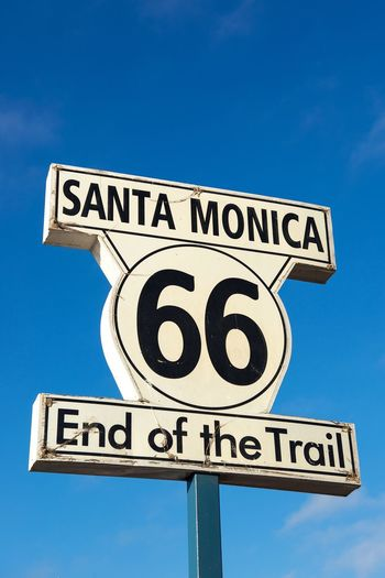 End Of The Trail End Route 66 Santa Monica California Pier Guidance Road Sign Communication Text Directional Sign Copy Space Direction Blue Arrow Symbol Marker 66 Motherroad Low Angle View Outdoors No People Clear Sky Street Name Sign Sky Close-up