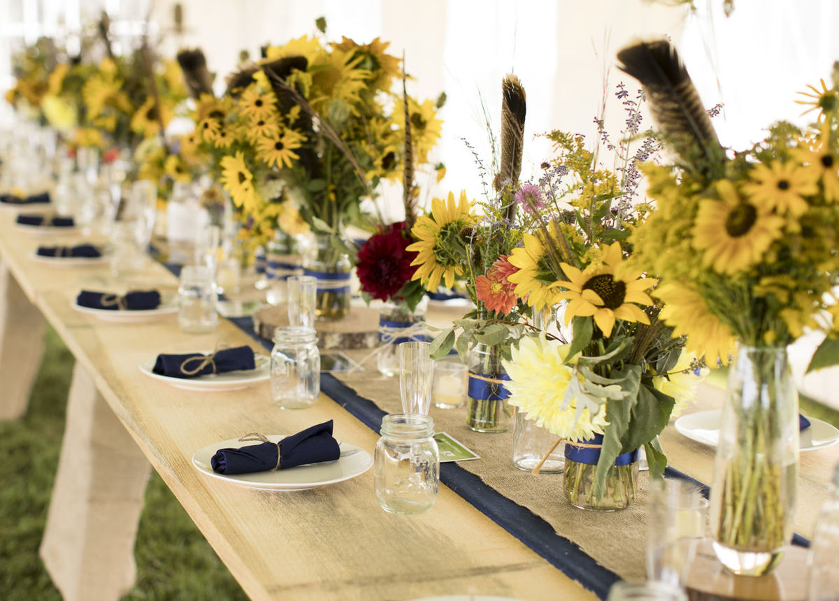 Summer wedding reception in a tent outdoors - featuring flowers grown by the bride Farm Farm Wedding Nature Reception Hall Rustic Summer Bouquet Sunflower Wedding Wedding Flowers Wedding Reception Bouquet Dinner Table Diy Wedding Farm Style Feather  Flowers Outdoor Wedding Place Setting Plate Rustic Wedding Summer Summer Wedding  Tent Wildflower Bouquet Wildflowers