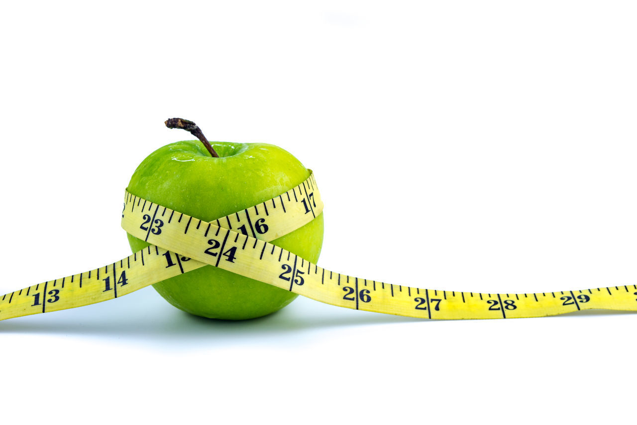 Green apple wrapped with a yellow measuring tape on white background Apple Calm Collection Green Green Color Healthy Eating Measuring Tape Number Obesity Slim Studio Shot Tape Measure