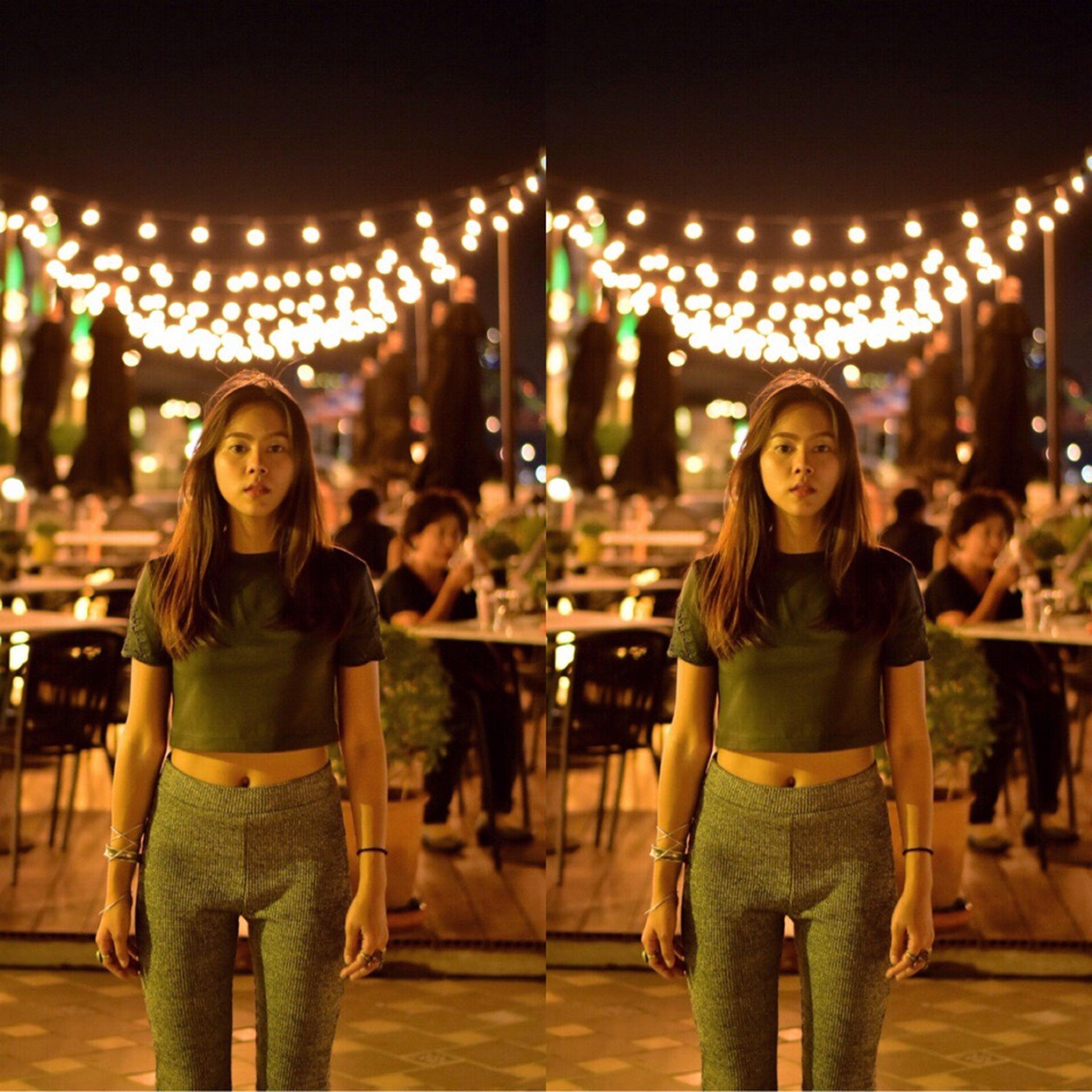 illuminated, leisure activity, standing, person, smiling, lighting equipment, happiness, lifestyles, night, young adult, casual clothing, celebration, front view, young women, looking at camera, focus on foreground, decoration, electric light, culture