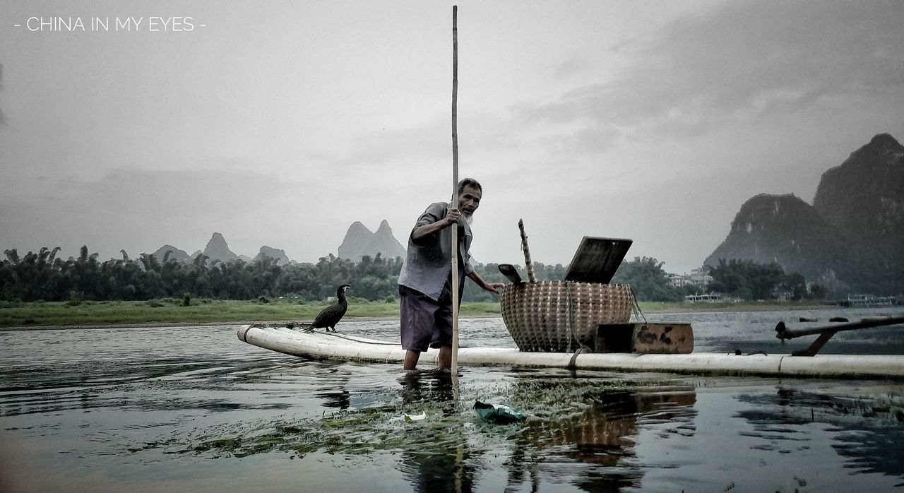 real people, water, nautical vessel, full length, men, nature, sky, day, occupation, mode of transport, basket, wooden raft, transportation, outdoors, mountain, waterfront, fisherman, casual clothing, one person, standing, holding, lake, lifestyles, beauty in nature, scenics, working, tree