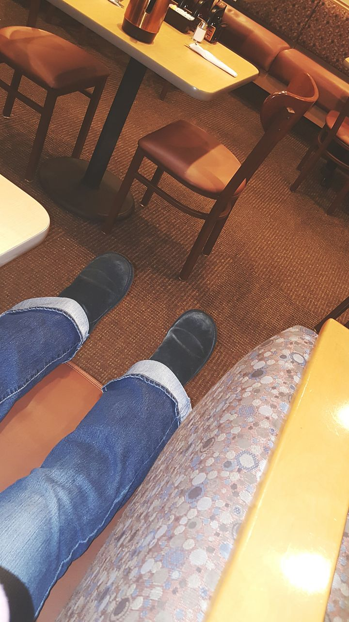 low section, human leg, one person, real people, shoe, jeans, human body part, high angle view, men, lifestyles, sitting, indoors, day, standing, human hand, close-up, people