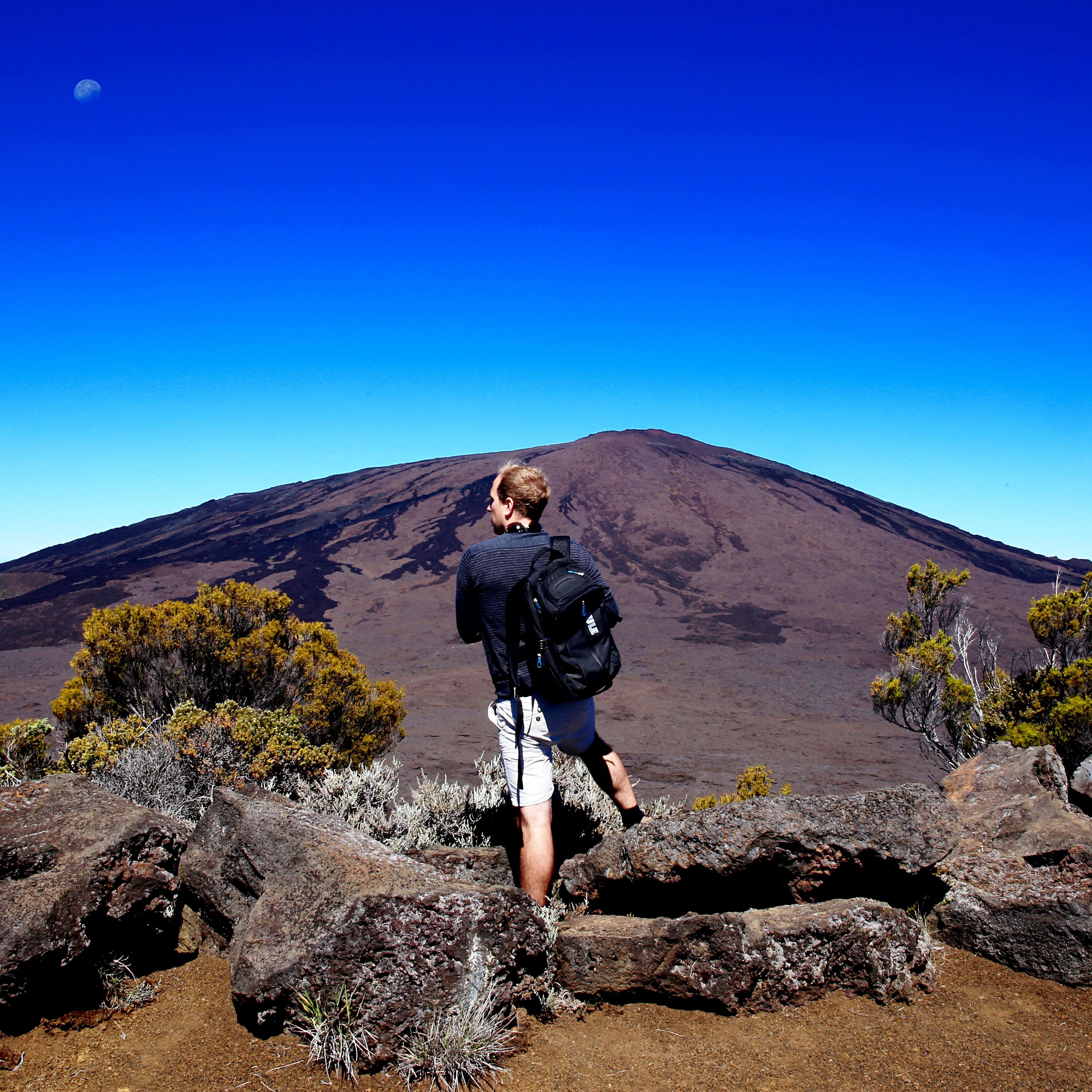 clear sky, copy space, blue, full length, lifestyles, leisure activity, casual clothing, sunlight, standing, rock - object, mountain, young adult, young men, nature, men, day, rear view, landscape