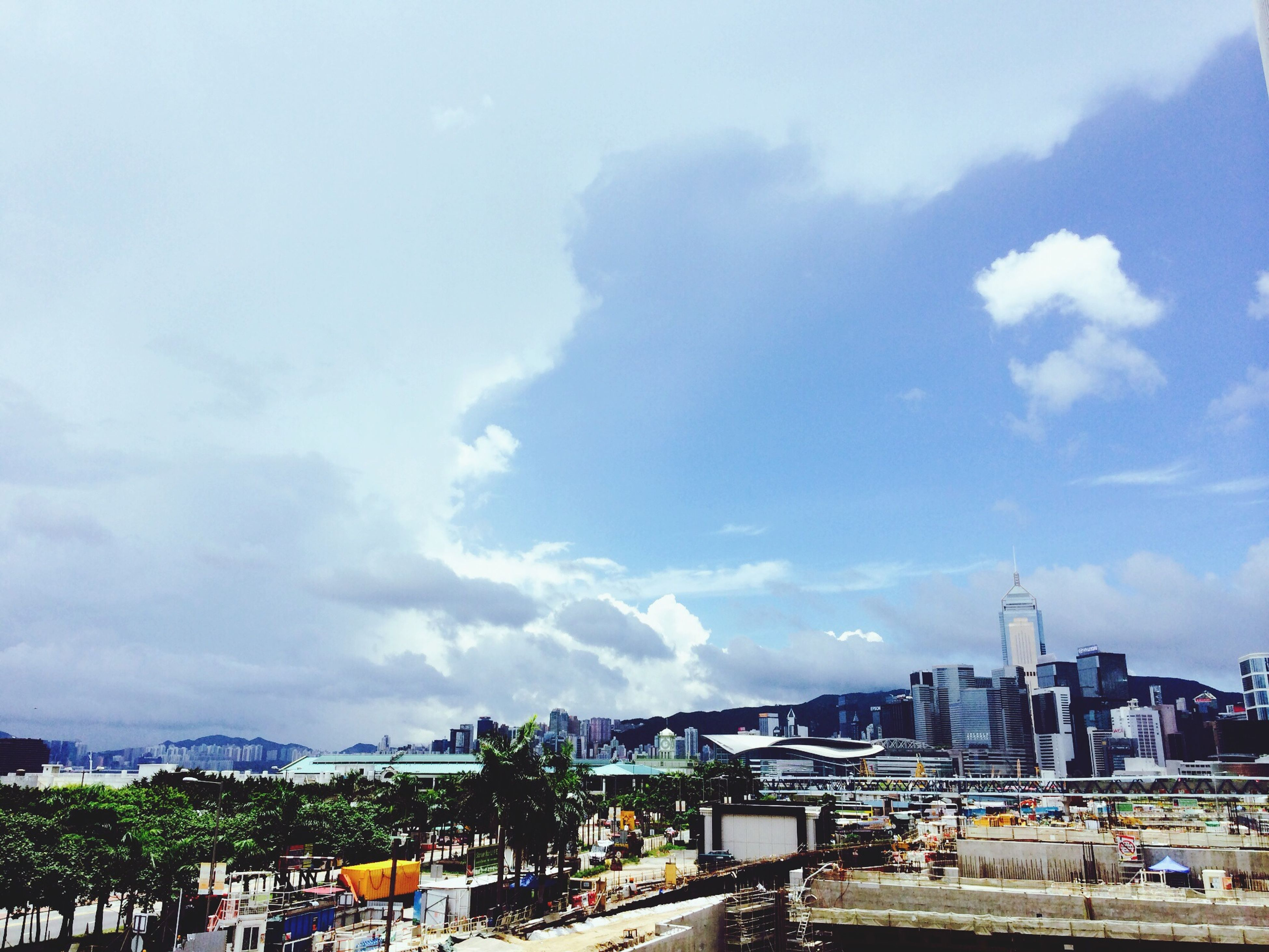 sky, building exterior, built structure, architecture, cloud - sky, transportation, cloudy, city, cloud, mode of transport, road, day, car, cityscape, outdoors, street, residential building, high angle view, no people, land vehicle