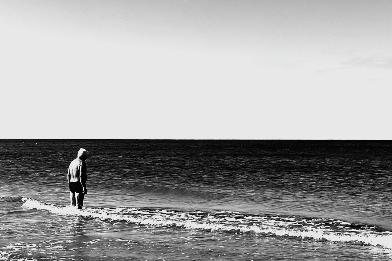 sea, horizon over water, copy space, water, full length, clear sky, beach, rear view, scenics, real people, standing, walking, nature, beauty in nature, tranquil scene, outdoors, men, sky, vacations, lifestyles, wave, day, ankle deep in water, young adult, people