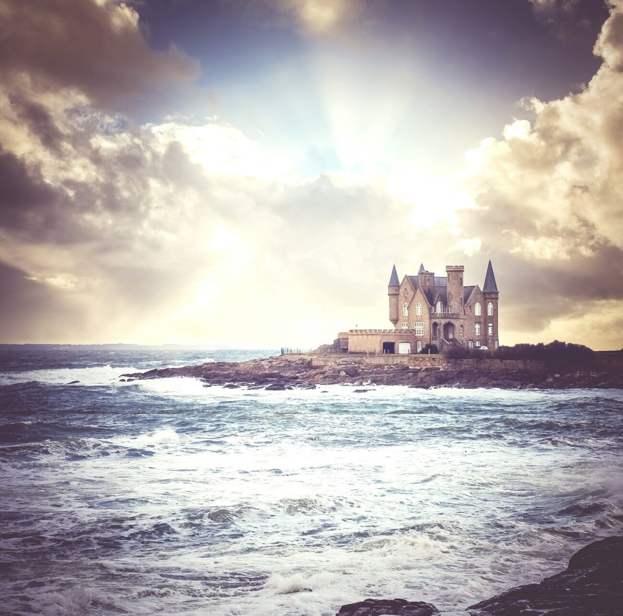 sea, water, architecture, sky, history, built structure, castle, cloud - sky, travel destinations, building exterior, wave, beauty in nature, no people, nature, outdoors, scenics, day, sunset, horizon over water