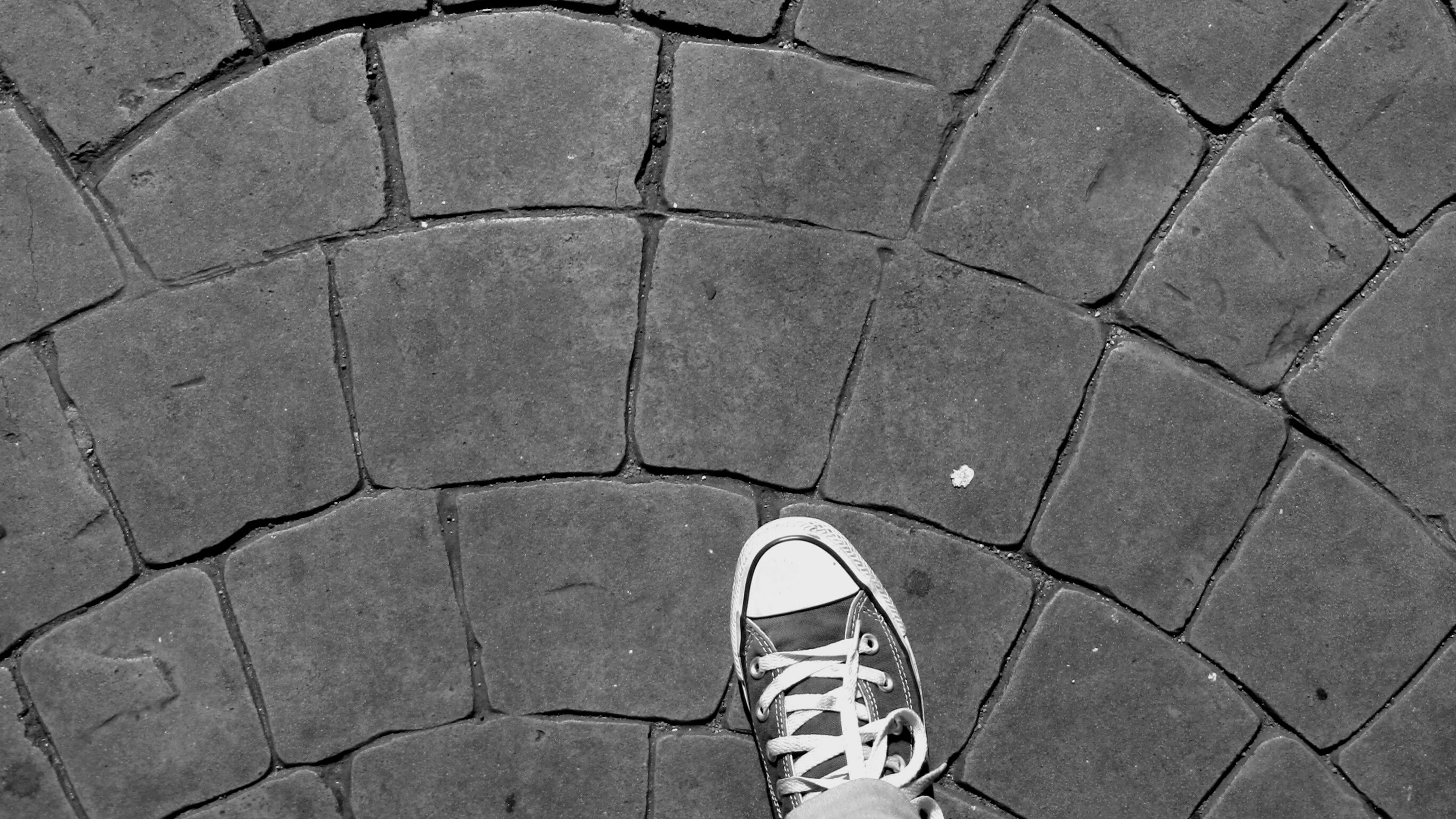 cobblestone, high angle view, paving stone, pattern, footpath, street, shoe, directly above, day, outdoors, low section, pavement, tiled floor, sidewalk, circle, sunlight, standing, geometric shape