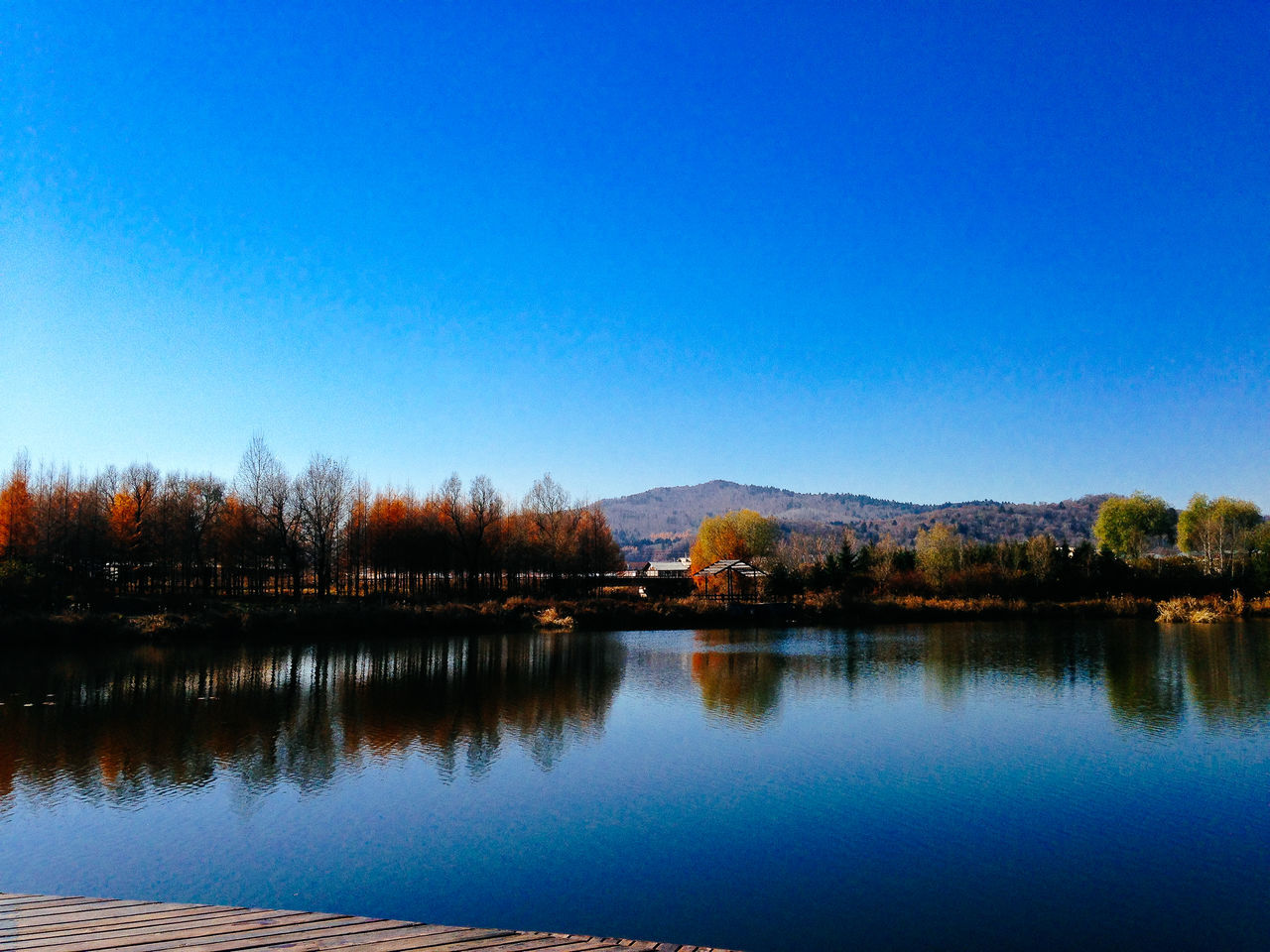 reflection, blue, tranquil scene, water, nature, tranquility, scenics, mountain, beauty in nature, lake, no people, outdoors, clear sky, tree, built structure, landscape, architecture, mountain range, sky, day