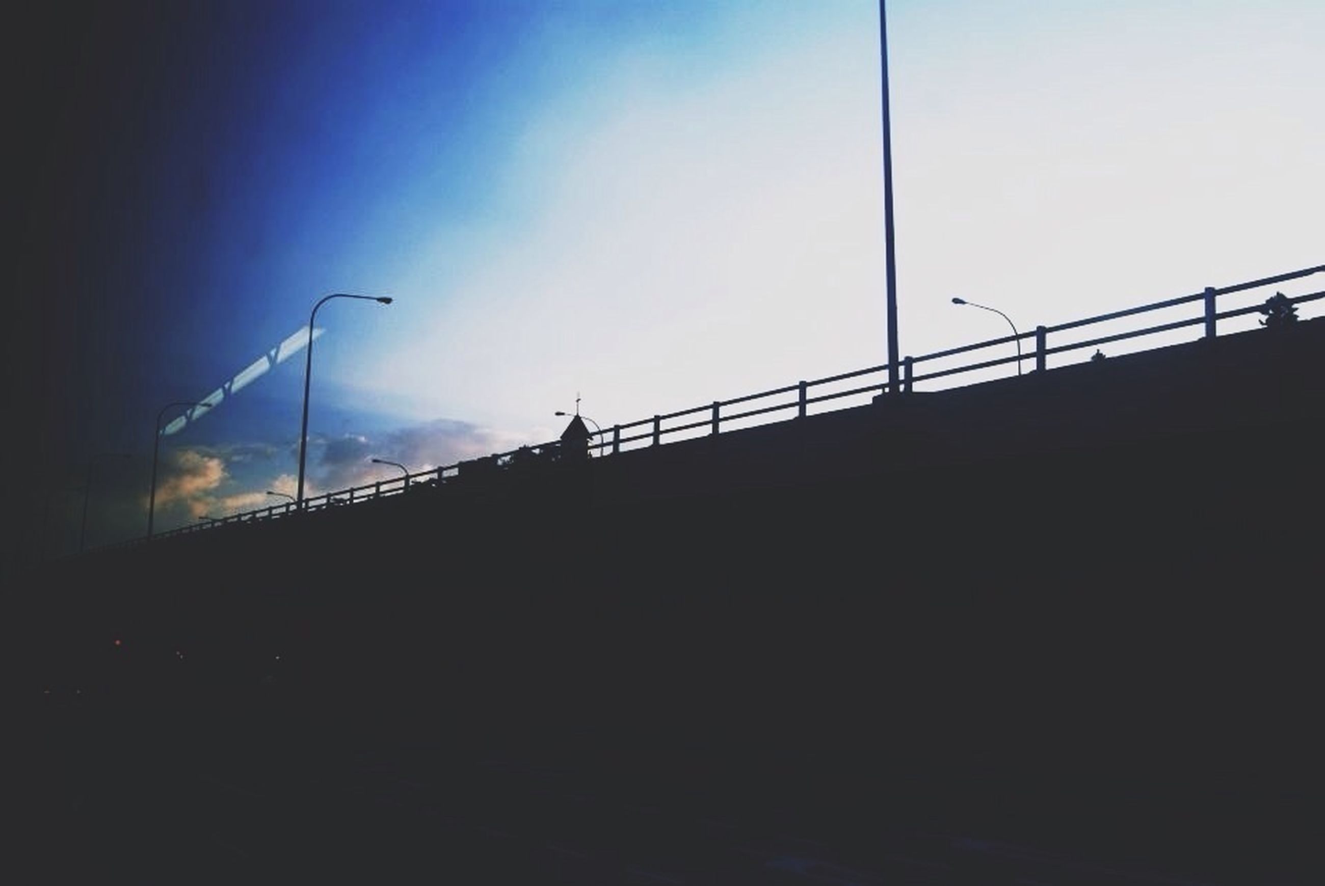 silhouette, railing, built structure, sky, low angle view, architecture, copy space, connection, bridge - man made structure, clear sky, dusk, bridge, street light, sunlight, sunset, outdoors, building exterior, day