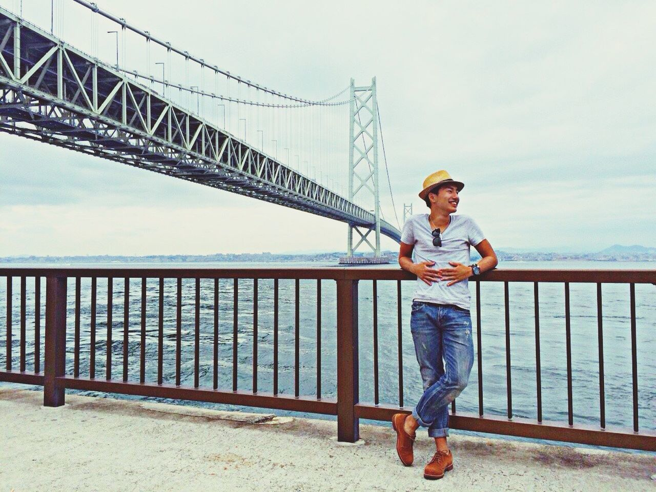 connection, railing, one person, bridge - man made structure, full length, smiling, standing, casual clothing, outdoors, day, architecture, suspension bridge, sky, built structure, real people, headwear, portrait, water, young adult, adult, people