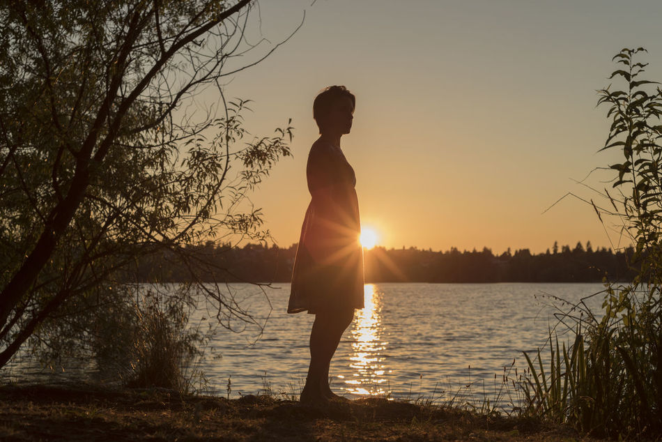 Silhouetted woman warm summer sunset at the lake Beauty In Nature Day Full Length Growth Lake Leisure Activity Lifestyles Nature One Person Outdoors Real People Scenics Side View Silhouette Sky Standing Sun Sunlight Sunset Tranquility Tree Water Women Young Adult Young Women