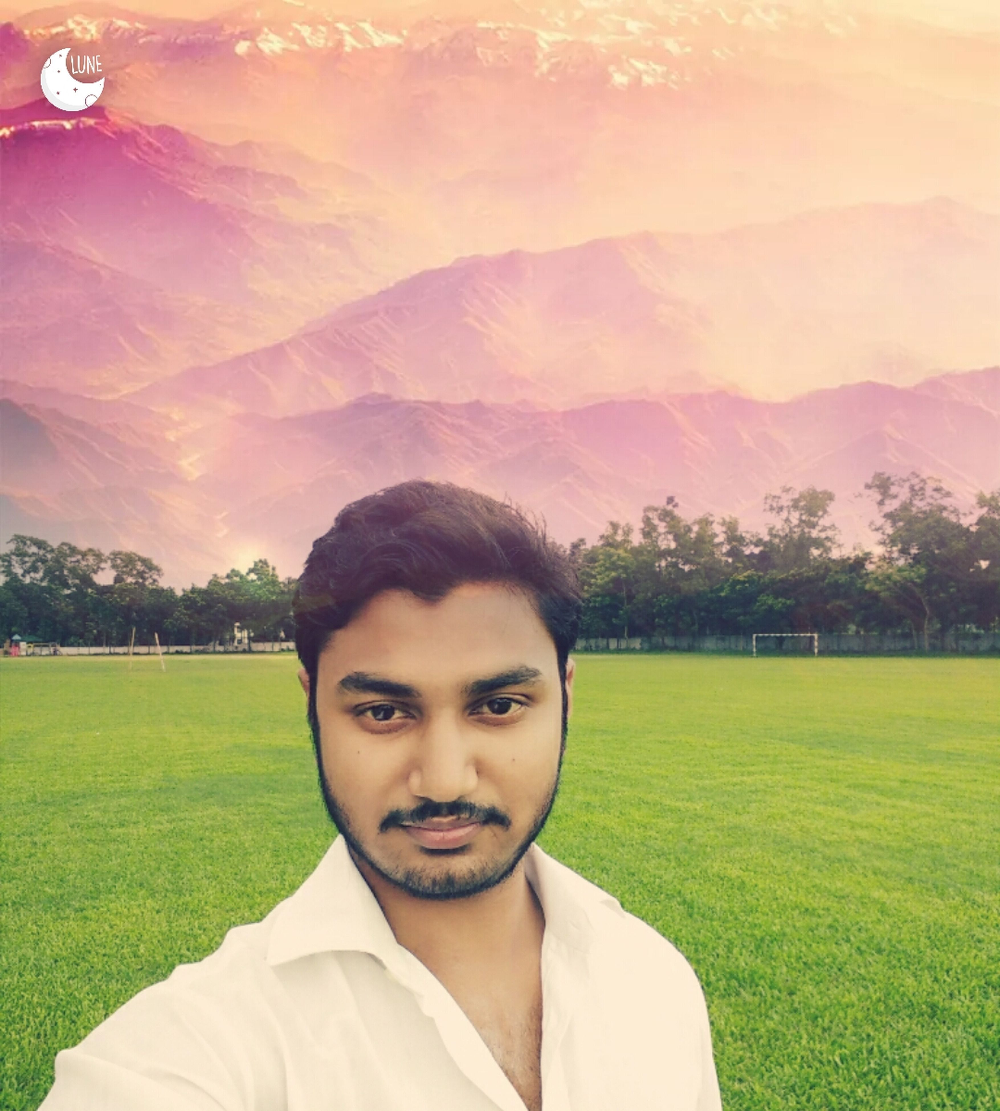 portrait, grass, lifestyles, leisure activity, headshot, field, mountain, casual clothing, green color, landscape, nature, sky, grassy, day, outdoors, beauty in nature, focus on foreground, toothy smile, tranquility, lawn