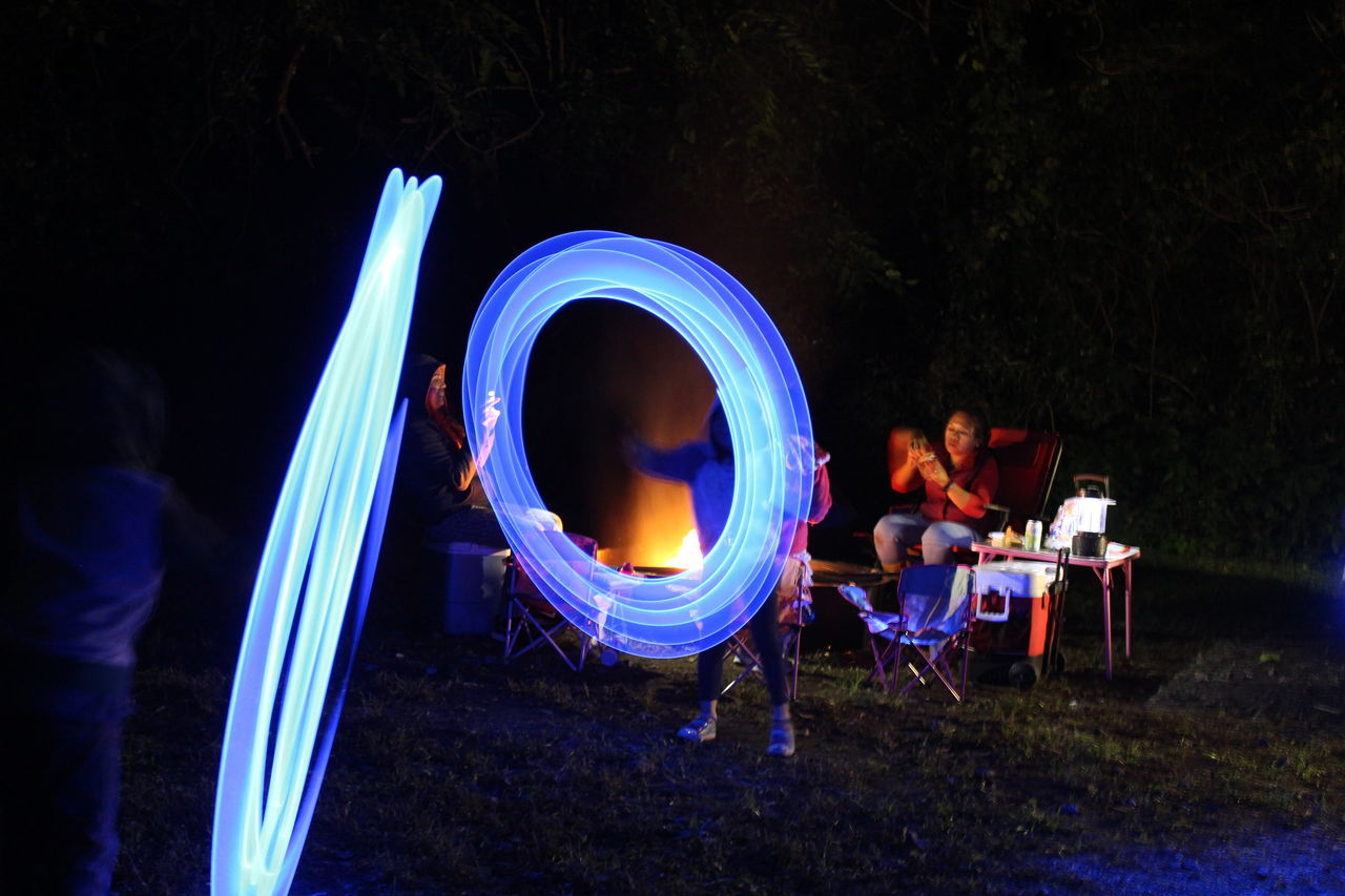 The kids having fun with their glow lights next to the camp fire. Camp Out Camping Crazy Lights Glowing Illuminated Night Outdoors