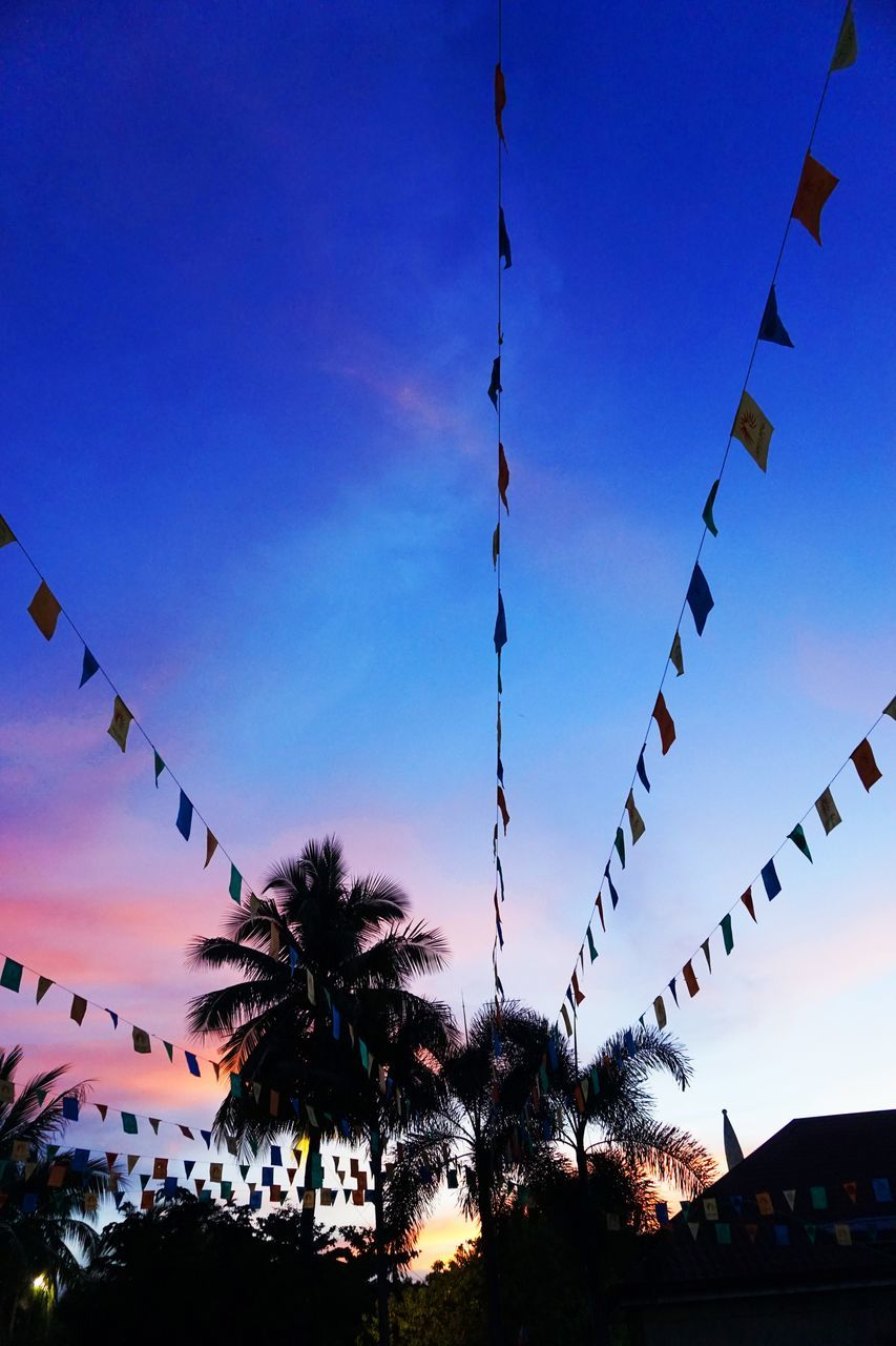 low angle view, celebration, hanging, outdoors, multi colored, silhouette, sky, tree, no people, bunting, building exterior, built structure, nature, architecture, sunset, beauty in nature, palm tree, clear sky, day