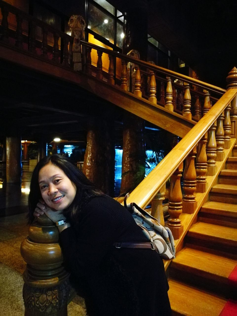 real people, night, young women, young adult, one person, lifestyles, railing, front view, leisure activity, smiling, illuminated, happiness, looking at camera, standing, built structure, portrait, architecture, alcohol, indoors