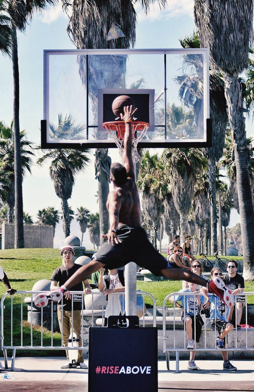 People Watching Shirtless Man Jumping To Put Basketball In Hoop