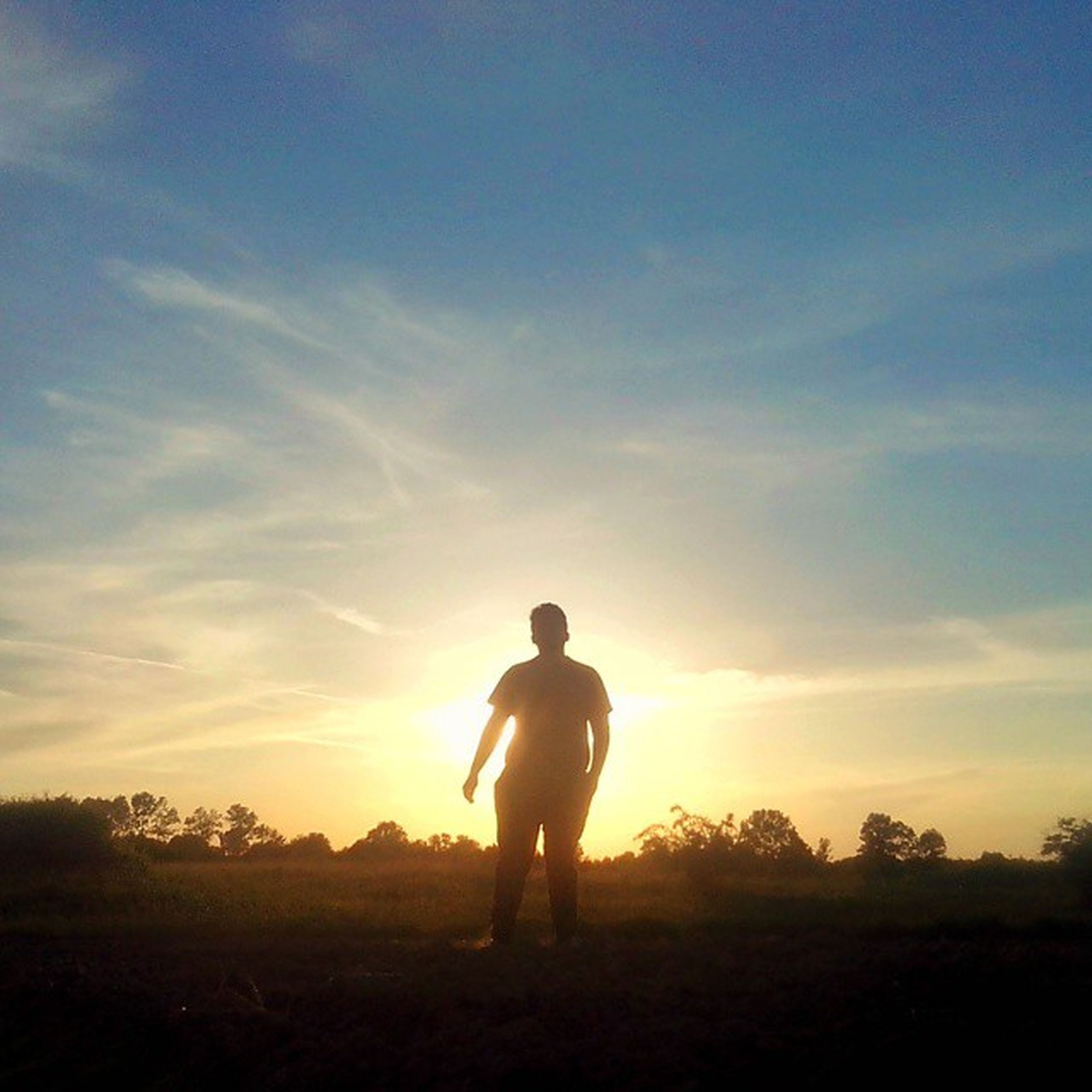 full length, leisure activity, lifestyles, sky, silhouette, sunset, standing, field, tranquil scene, tranquility, landscape, nature, beauty in nature, cloud - sky, scenics, men, grass, rear view