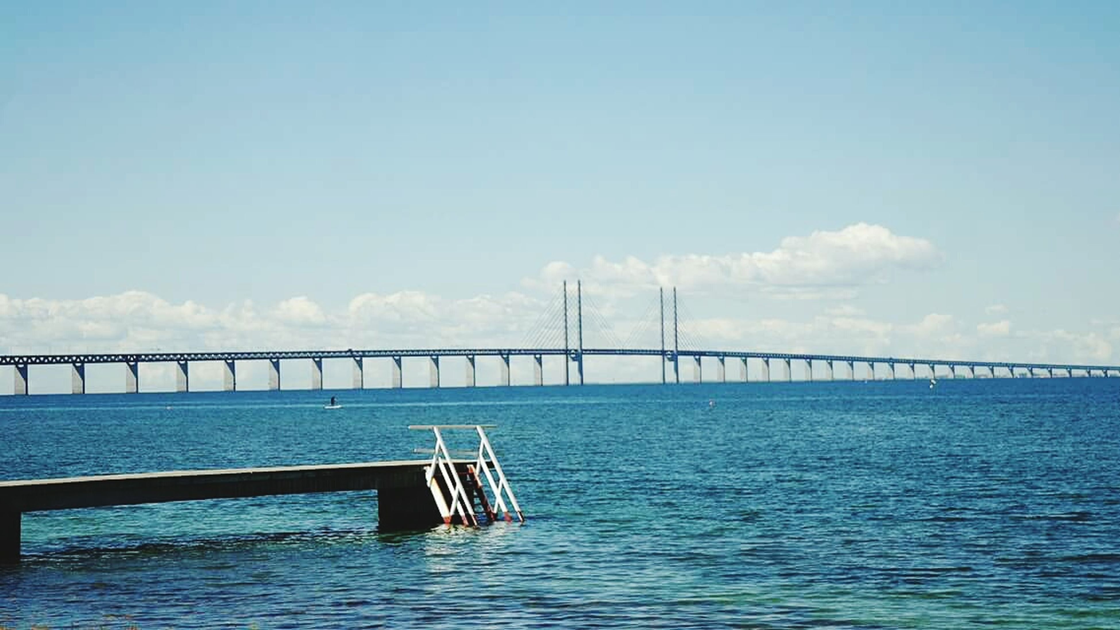 connection, water, bridge - man made structure, sky, sea, bridge, built structure, waterfront, transportation, architecture, rippled, engineering, river, tranquil scene, tranquility, blue, long, nature, cloud, suspension bridge
