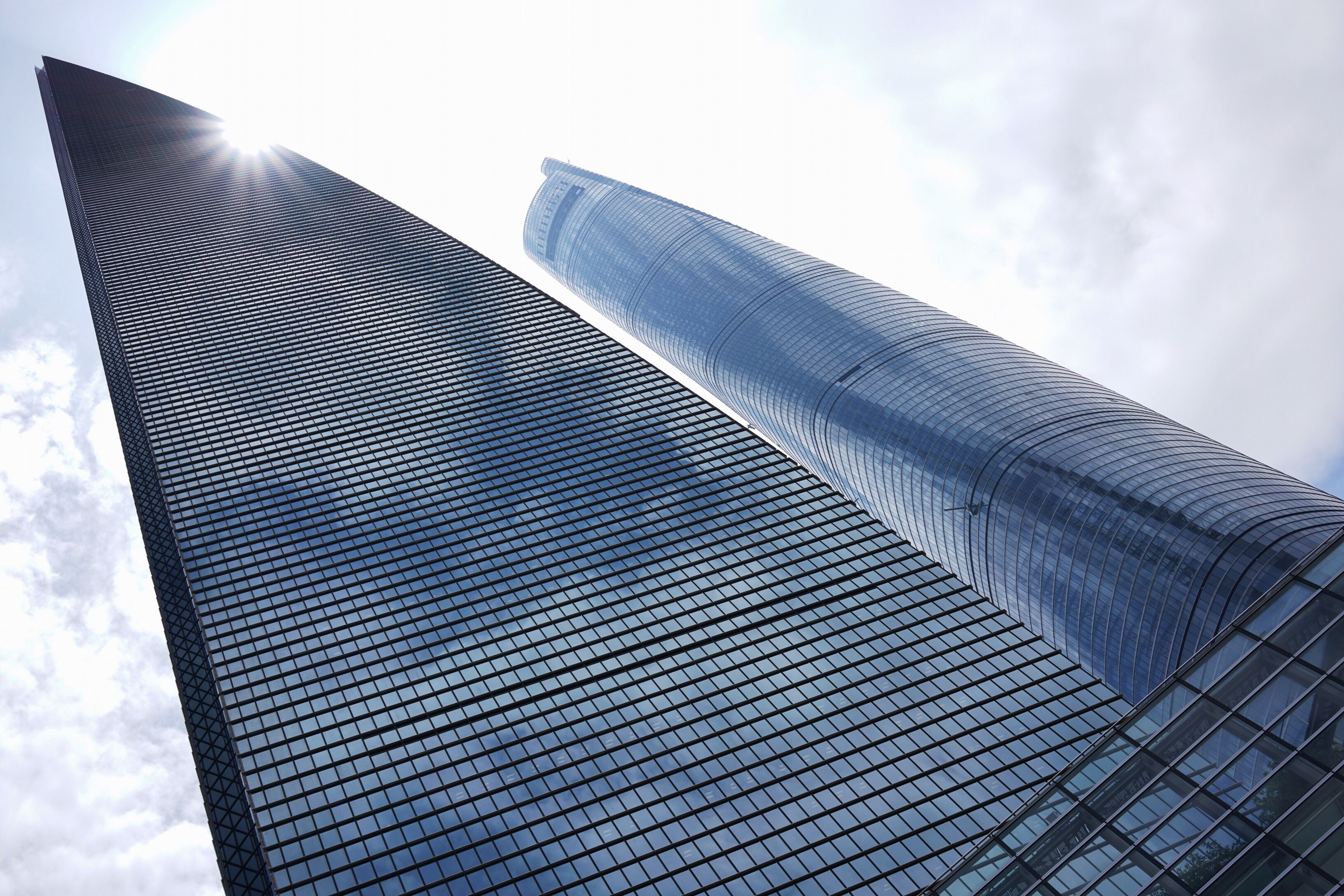 low angle view, modern, architecture, building exterior, built structure, office building, skyscraper, sky, tall - high, glass - material, city, tower, cloud - sky, building, reflection, day, pattern, cloud, outdoors, no people