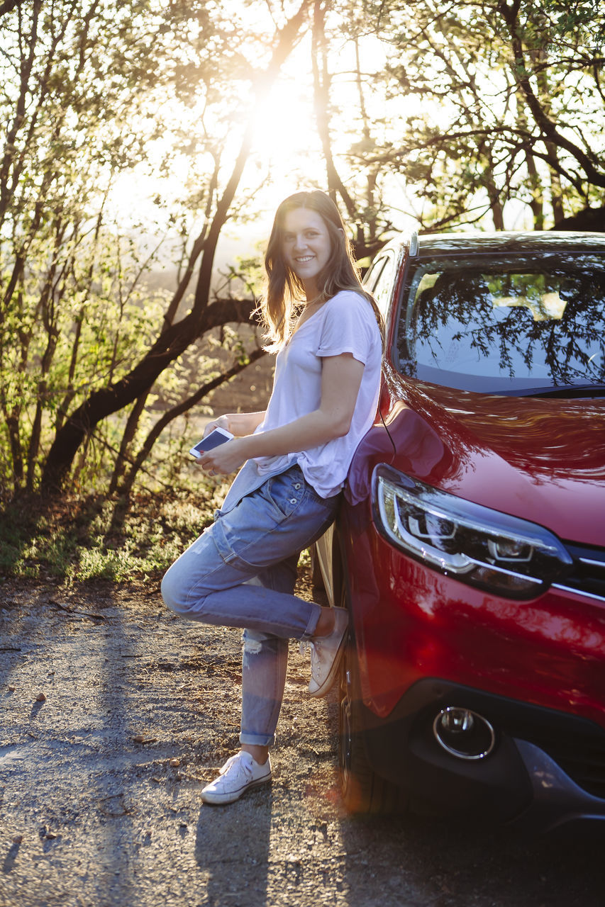 full length, real people, tree, young adult, one person, young women, leisure activity, car, lifestyles, casual clothing, outdoors, standing, beautiful woman, day, front view, tree trunk, transportation, looking at camera, portrait, happiness, posing, smiling, nature
