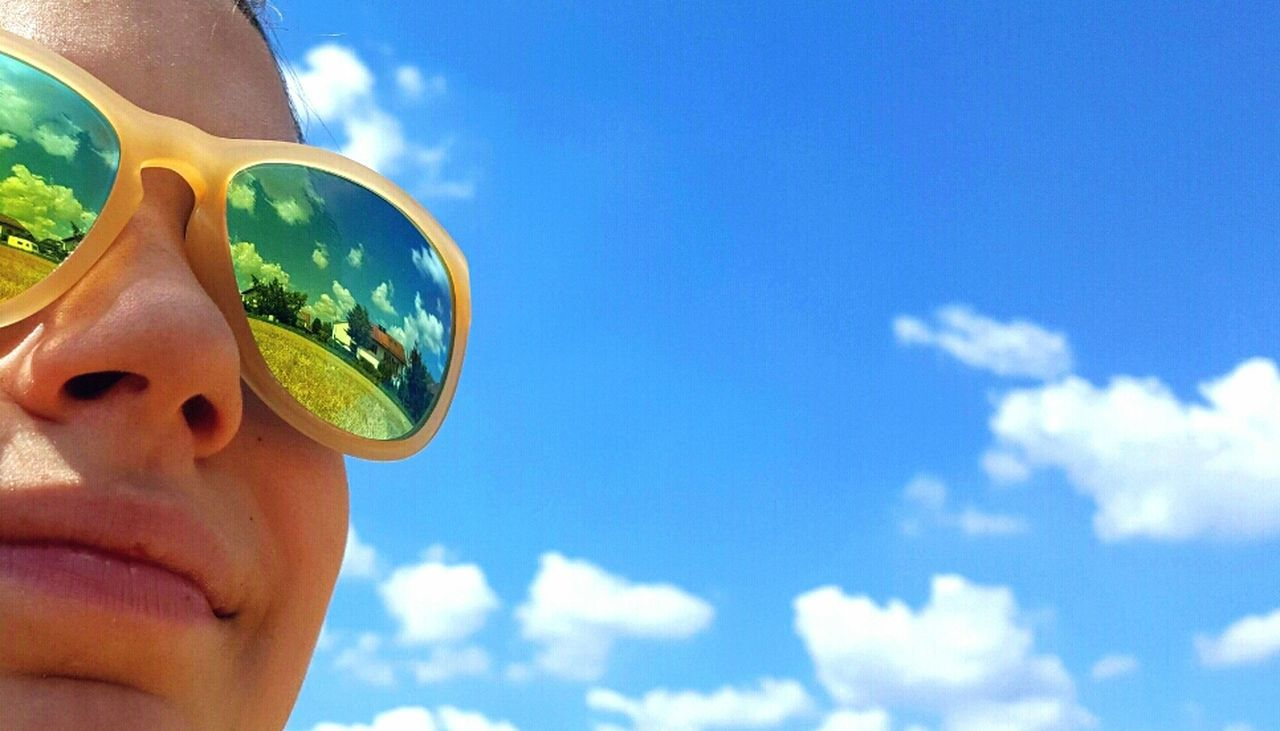 sunglasses, sky, cloud - sky, real people, childhood, day, outdoors, one person, leisure activity, blue, lifestyles, boys, sunlight, low angle view, looking at camera, eyewear, portrait, human face, vacations, swimming pool, smiling, nature, close-up, people