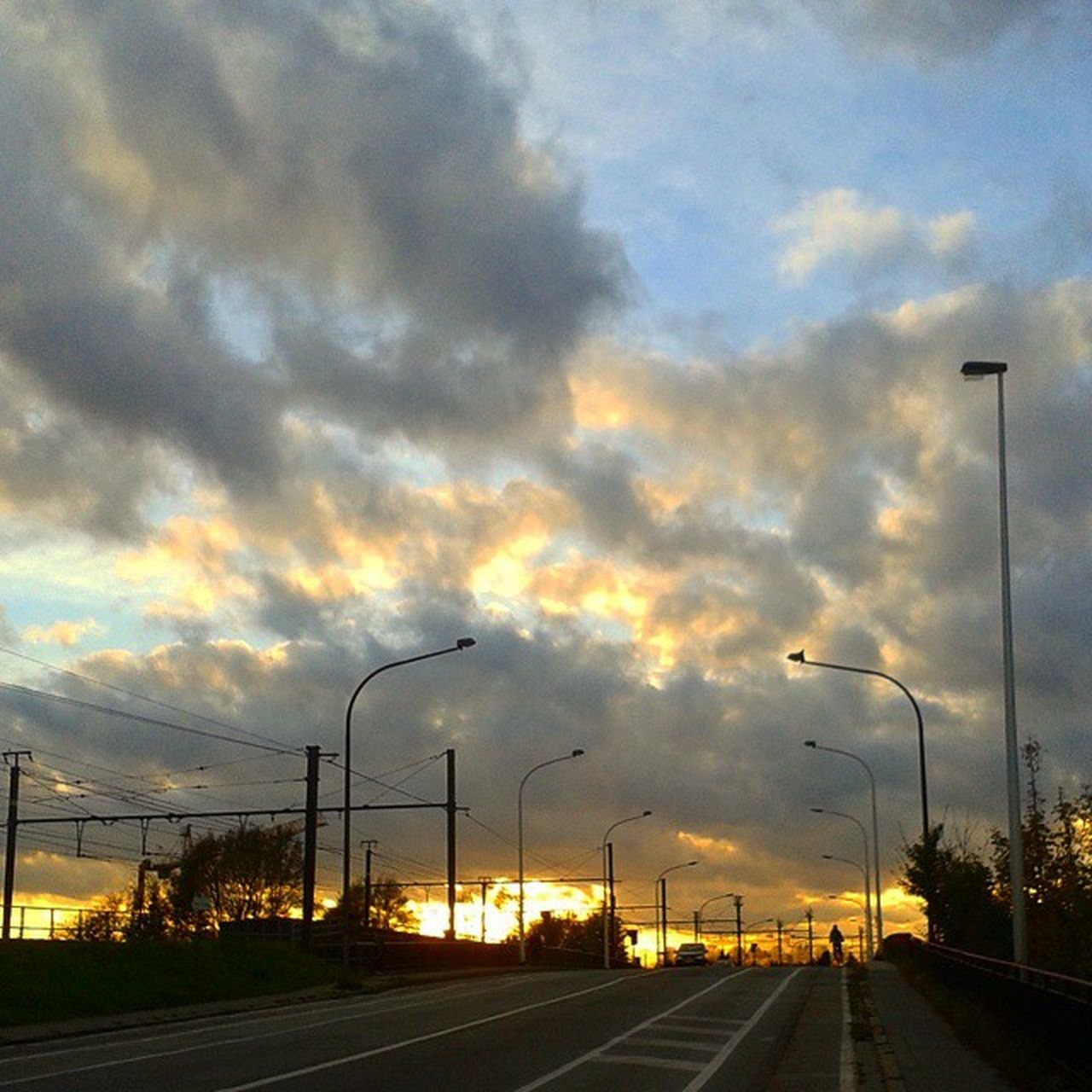 sky, cloud - sky, transportation, street light, no people, road, outdoors, electricity pylon, the way forward, sunset, tree, storm cloud, day, nature, city